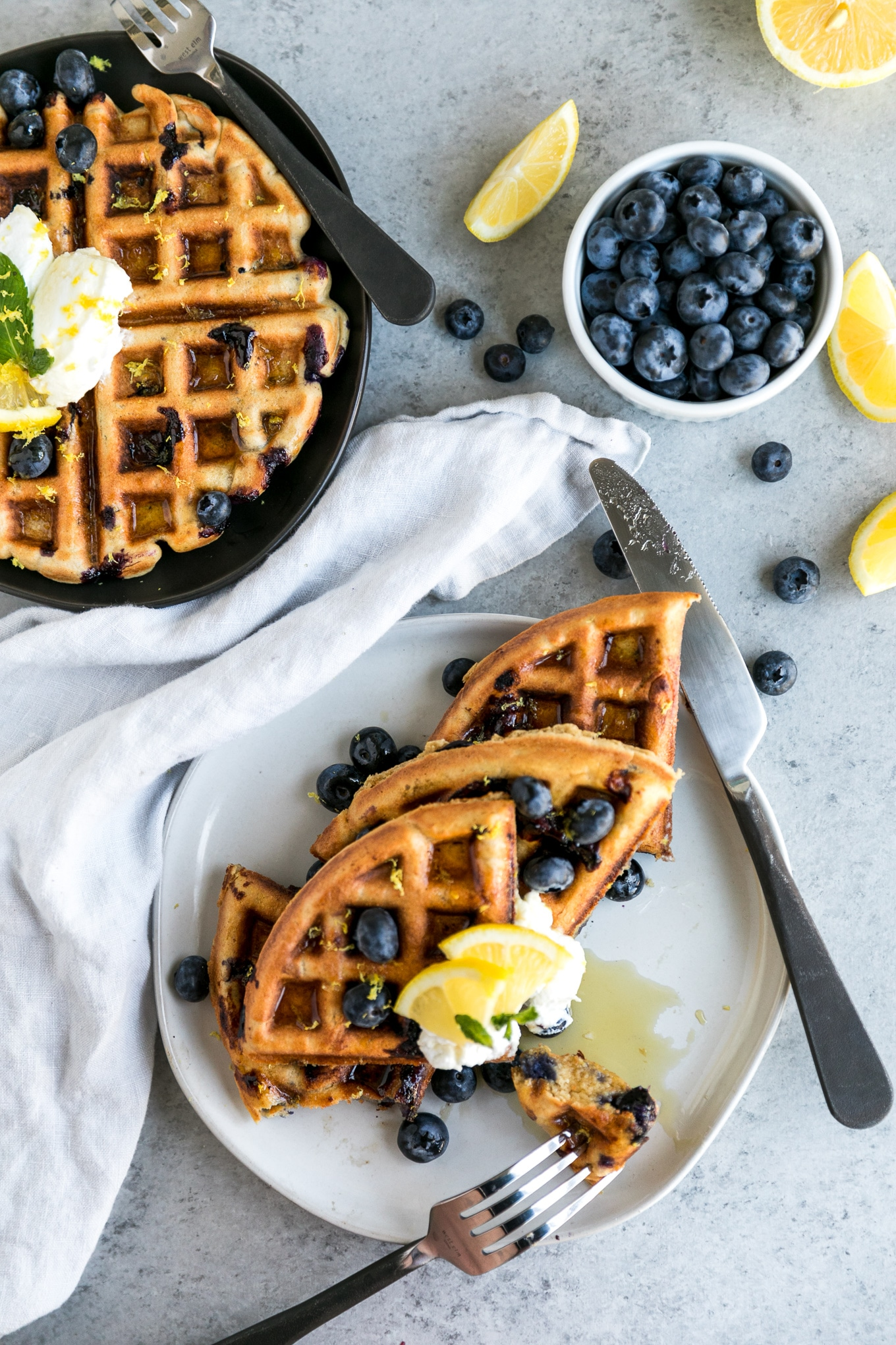 Overhead shot of two plates of waffles topped with blueberries, lemon slices, and a dollop of Greek yogurt