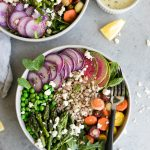 Overhead shot of two bowls of salad with asparagus, peas, watermelon radishes, purple daikon, carrots, farro, and feta