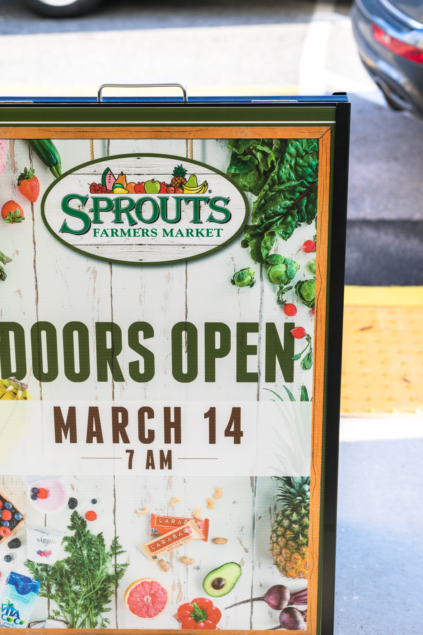Photo of a sign at a Sprouts grocery store saying that doors open March 14th at 7am
