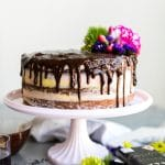 Straight on shot of a layer cake with pastel colored icing, chocolate ganache dripping down the cake, and flowers on top