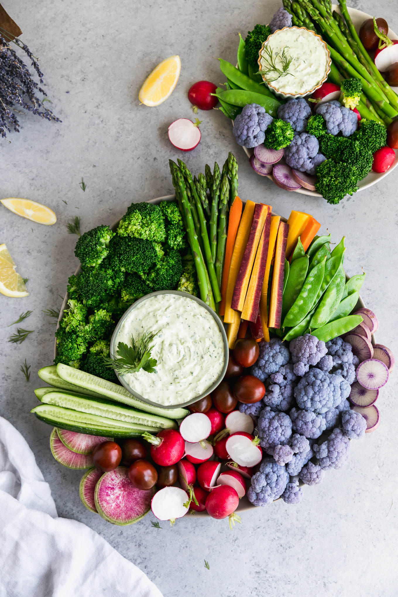 Overhead shot of a veggie platter with broccoli, asparagus, carrots, snap peas, purple cauliflower, radishes, and cucumbers, with a smaller veggie tray in the top right corner