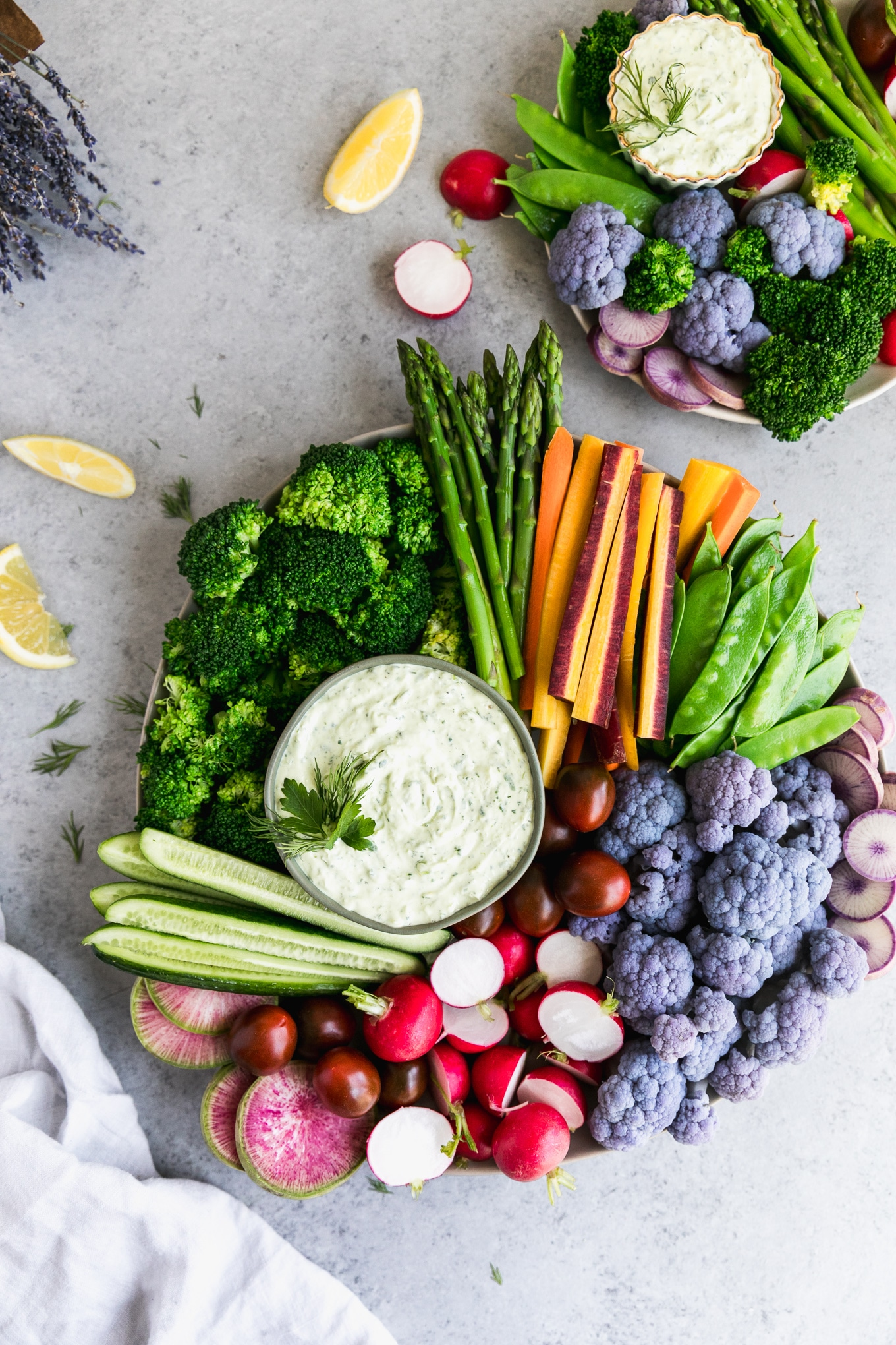 Overhead shot of a veggie platter with broccoli, asparagus, carrots, snap peas, purple cauliflower, radishes, and cucumbers, with a smaller veggie tray in the top right corner and a bouquet of lavender in the top left