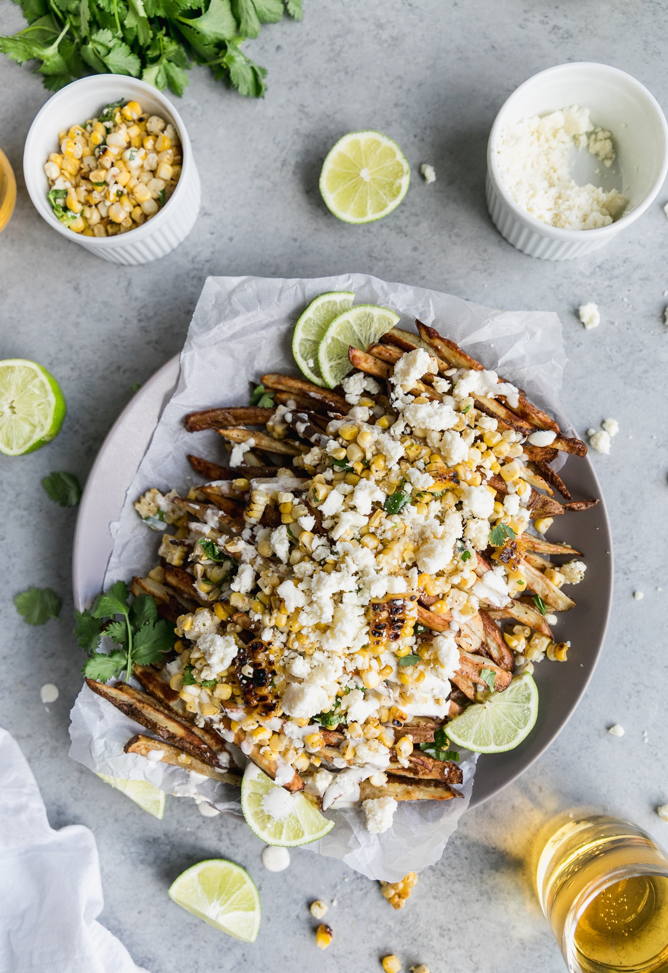 Overhead shot of fries topped with Mexican street corn, crema, lime wedges, and cilantro, with extra crumbled cotija cheese on top