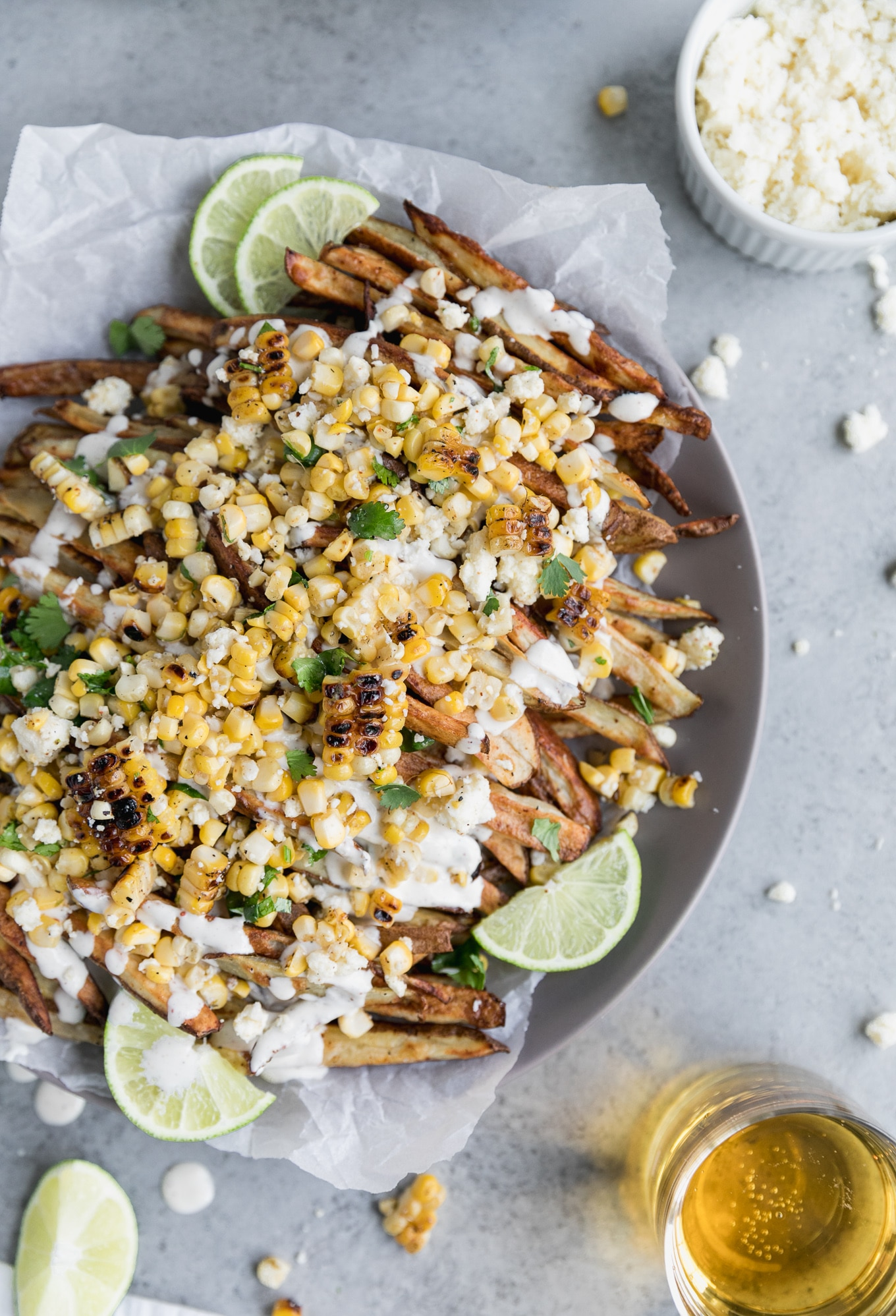 Overhead shot of golden brown fries topped with Mexican street corn, crema, lime wedges, and cilantro