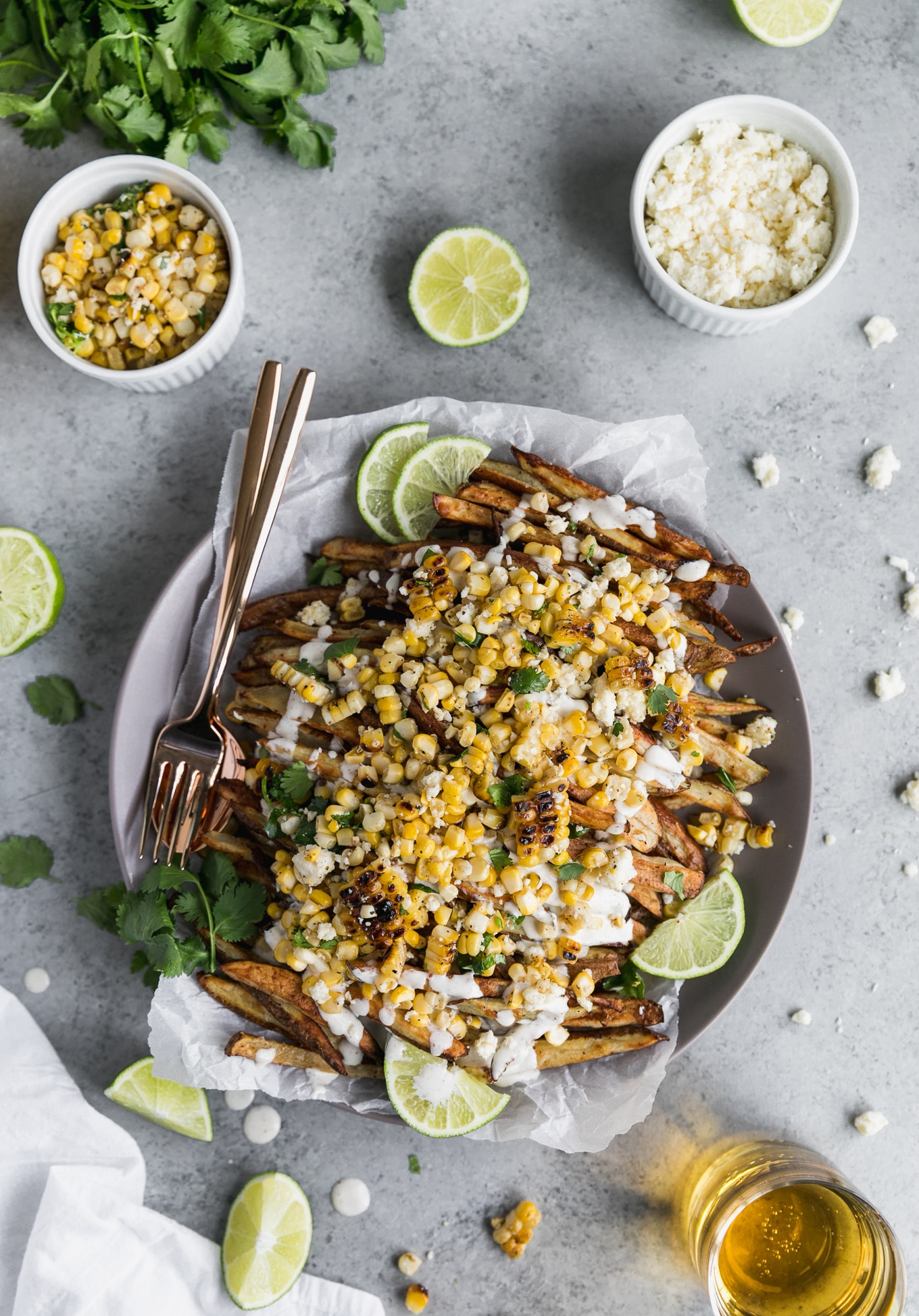 Overhead shot of fries topped with Mexican street corn, crema, lime wedges, and cilantro, with a fork and spoon resting on the plate, and a glass of beer in the bottom right corner
