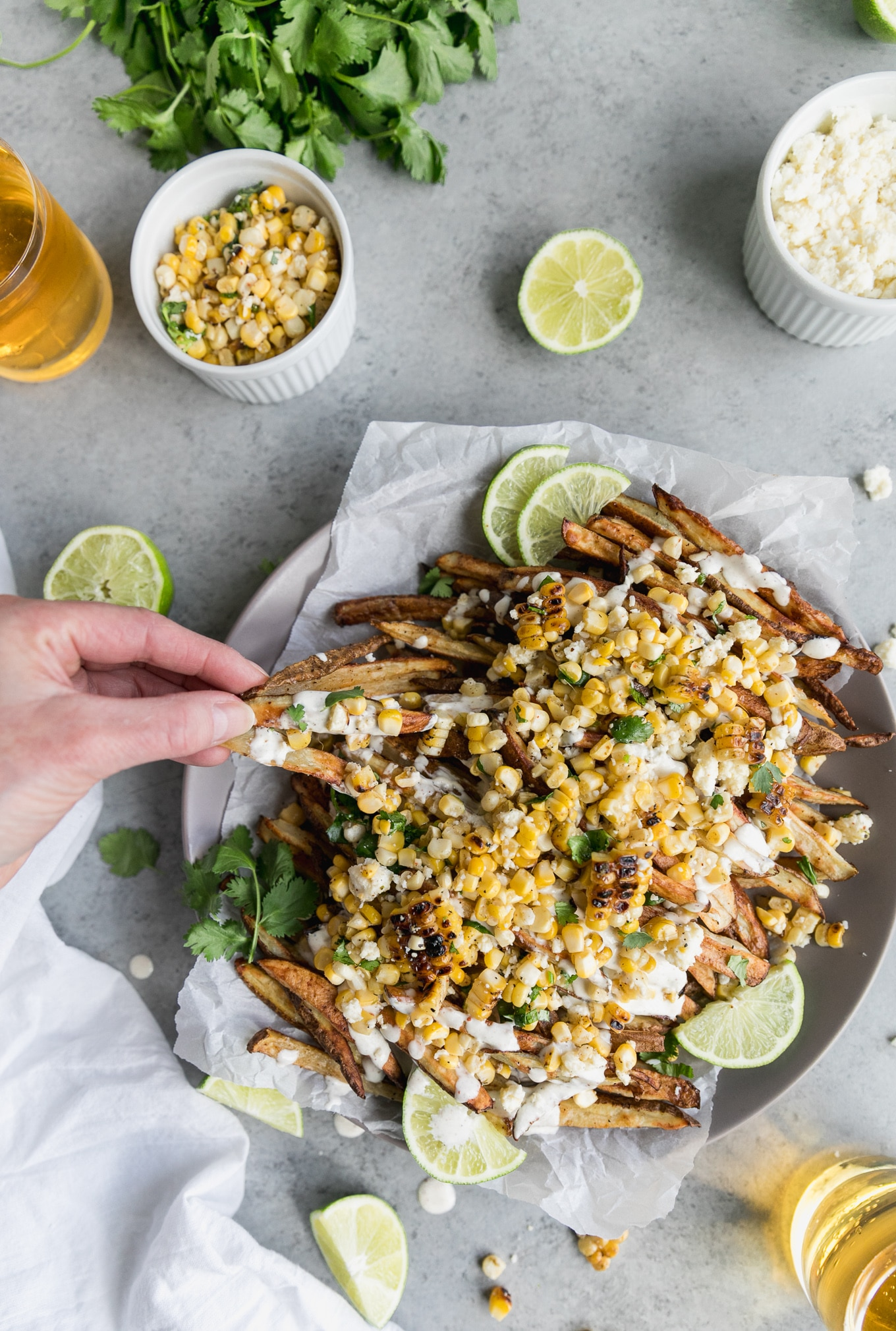 Overhead shot of fries topped with Mexican street corn, crema, lime wedges, and cilantro, with a fork and spoon resting on the plate, and a hand picking up a couple fries