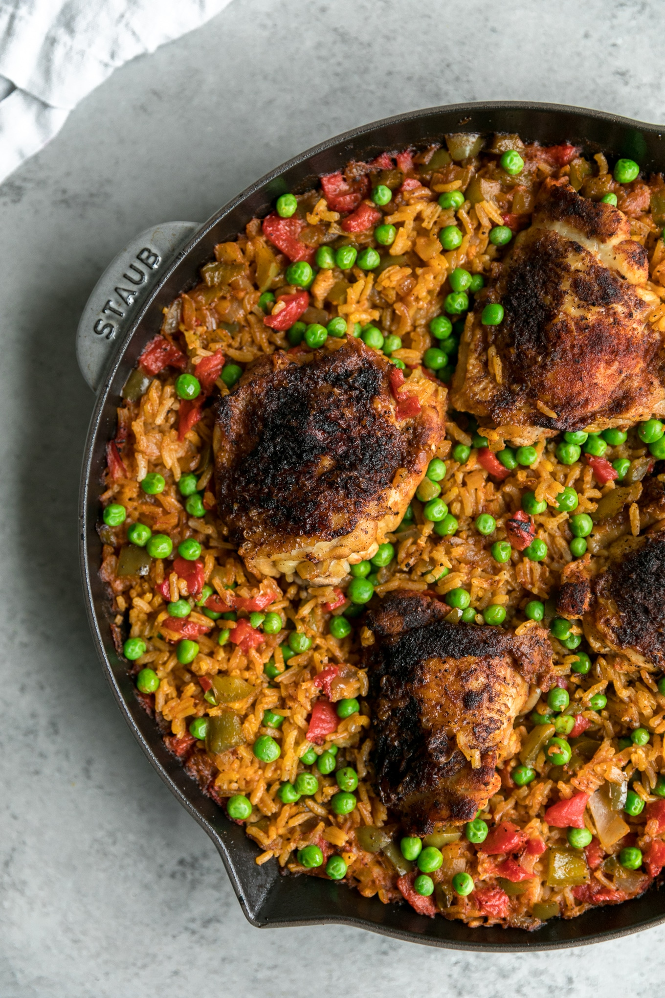 Overhead shot of a cast iron skillet filled with Spanish chicken and rice with peas