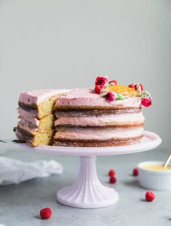 Forward facing shot of a three layer cake iced with pink icing, and a slice being pulled out of the left side of the cake