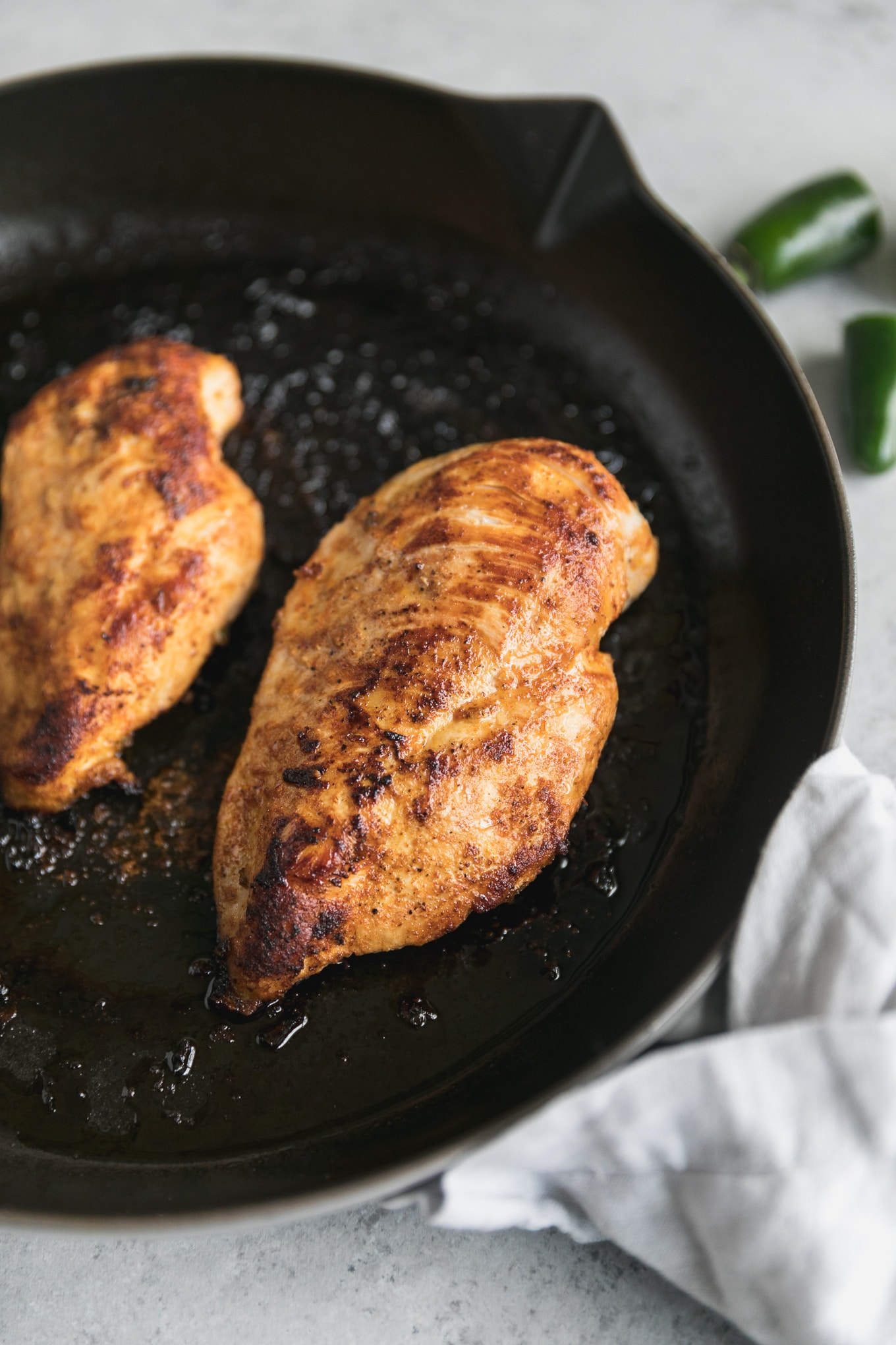 Close up shot of two golden brown chicken breasts cooked in a cast iron skillet