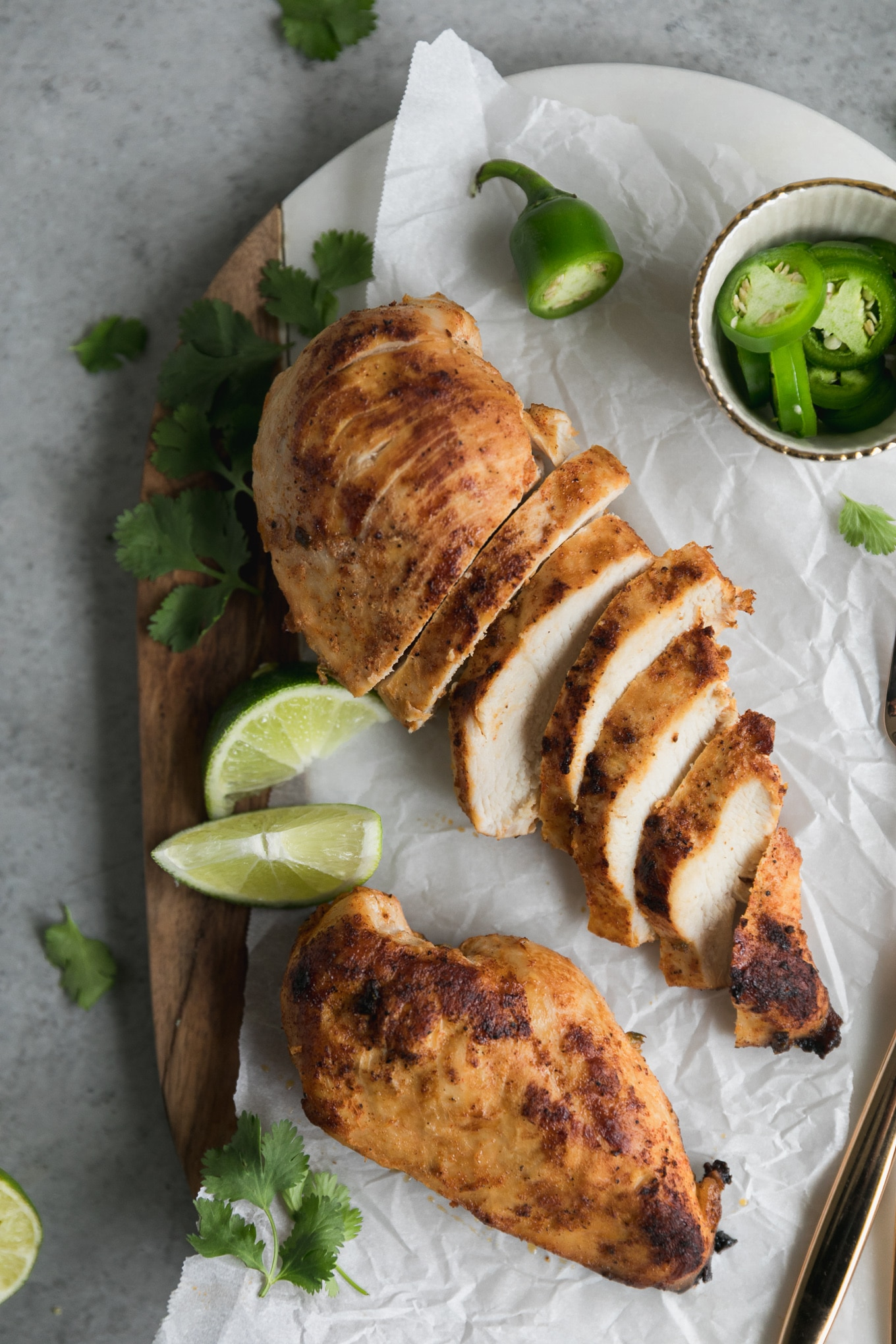Overhead shot of two chicken breasts, one sliced and one whole, with lime wedges, sliced jalapeños, and cilantro off to the side