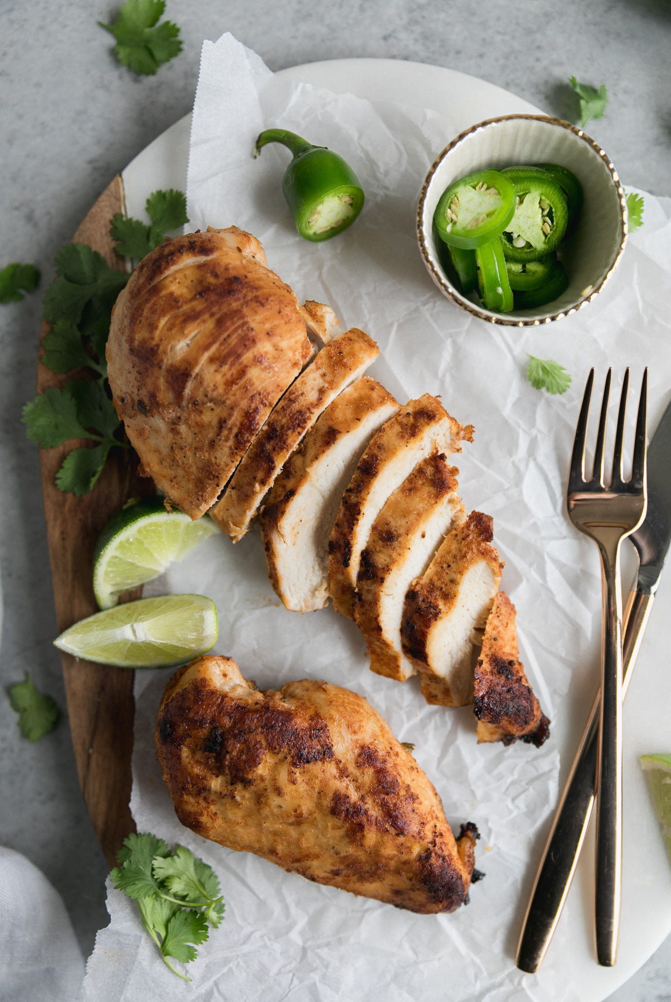 Overhead shot of two chicken breasts, one sliced and one whole, with lime wedges, a bowl of sliced jalapeños, and cilantro off to the side and a golf fork and knife to the right