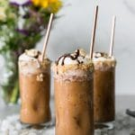 Forward facing shot of 3 iced coffees topped with whipped cream, toasted coconut, and chocolate sauce, with bronze straws in them and a vase of flowers in the background