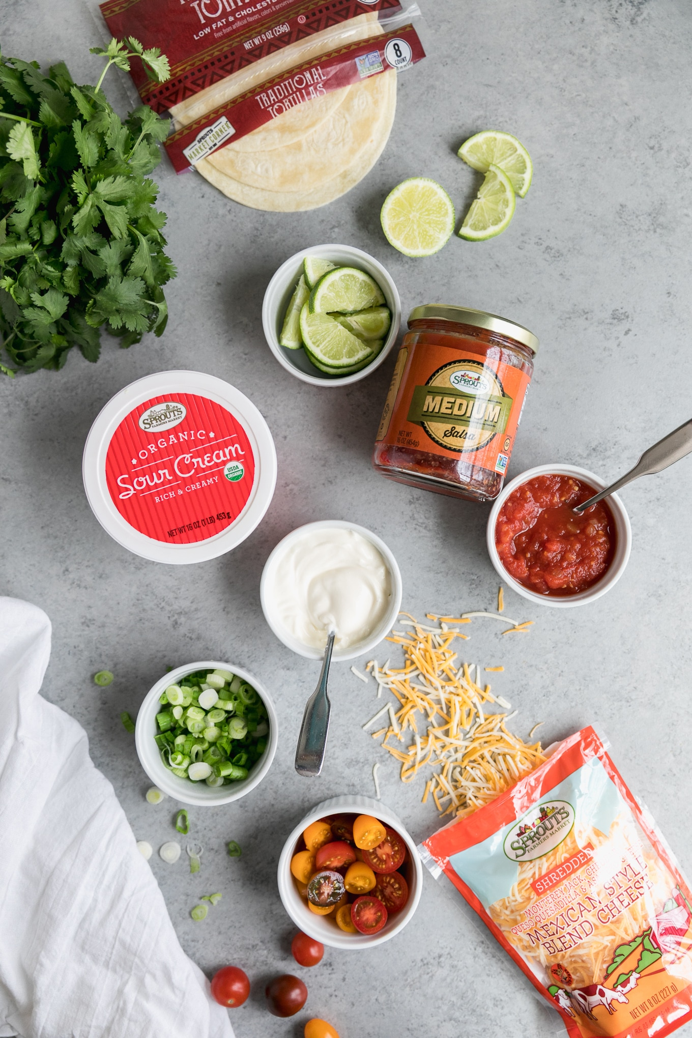 Overhead shot of small bowls filled with lime slices, sour cream, salsa, scallions, multicolored cherry tomatoes, a bag of tortillas, and a container of sour cream and a bag of cheese being spilled out in the bottom right corner