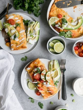 Overhead shot of two plates of enchiladas and a casserole dish of enchiladas with a bowl of cherry tomatoes, lime wedges, and sour cream off to the side