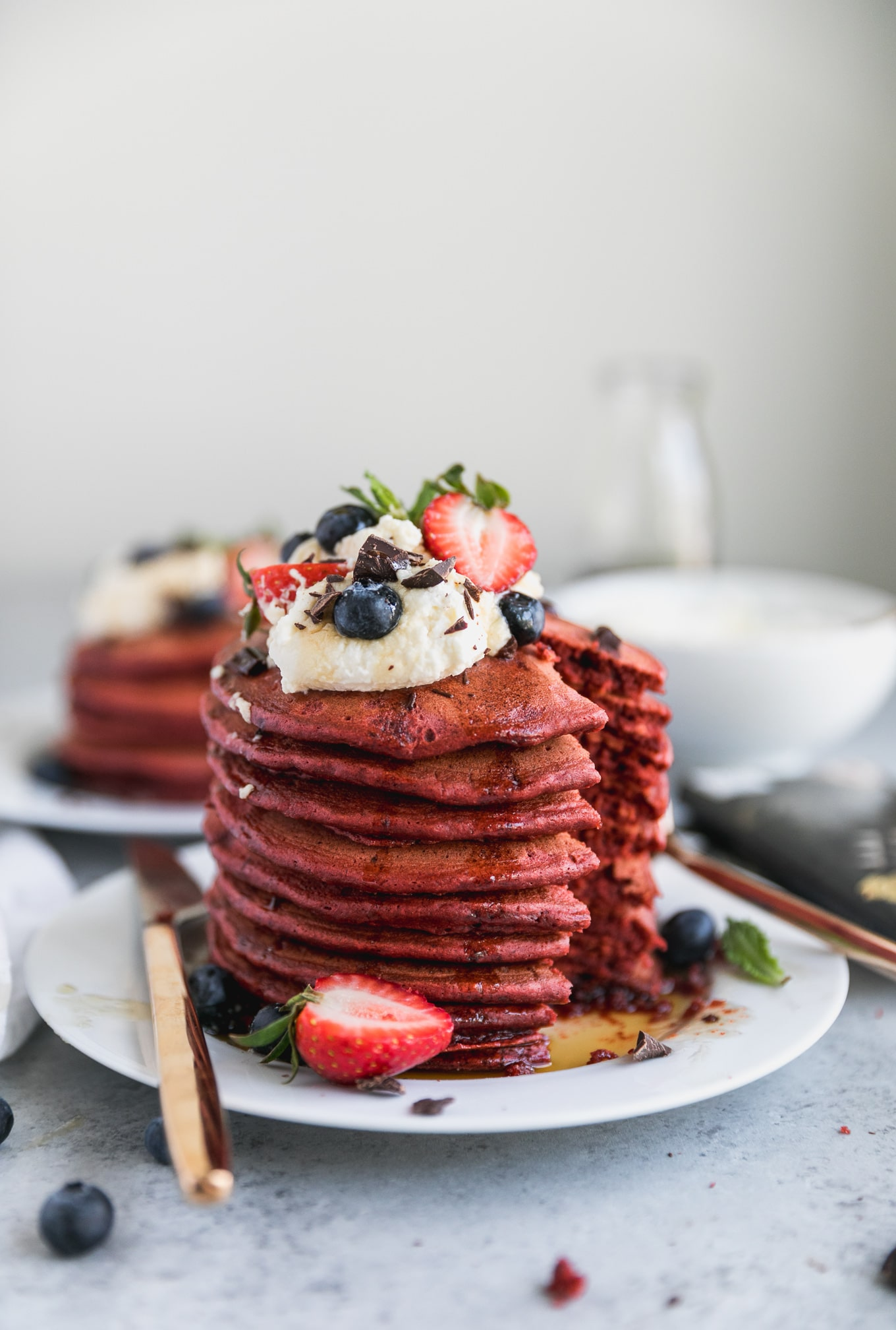 Forward facing shot of a stack of red velvet pancakes topped with whipped cream and berries with a bite taken out of them