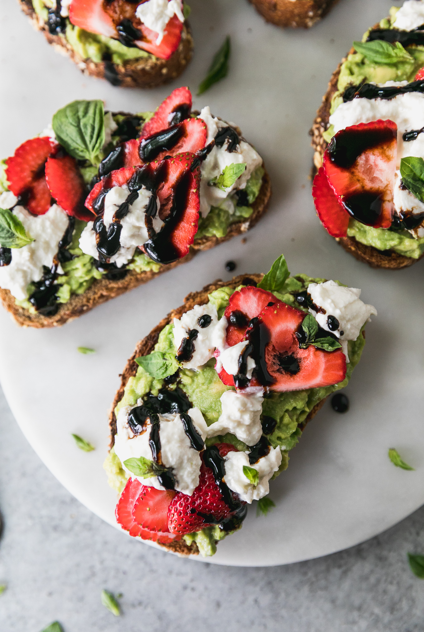 Overhead close up shot of three pieces of avocado toast topped with sliced strawberries, burrata cheese, fresh basil, and a drizzle of balsamic glaze