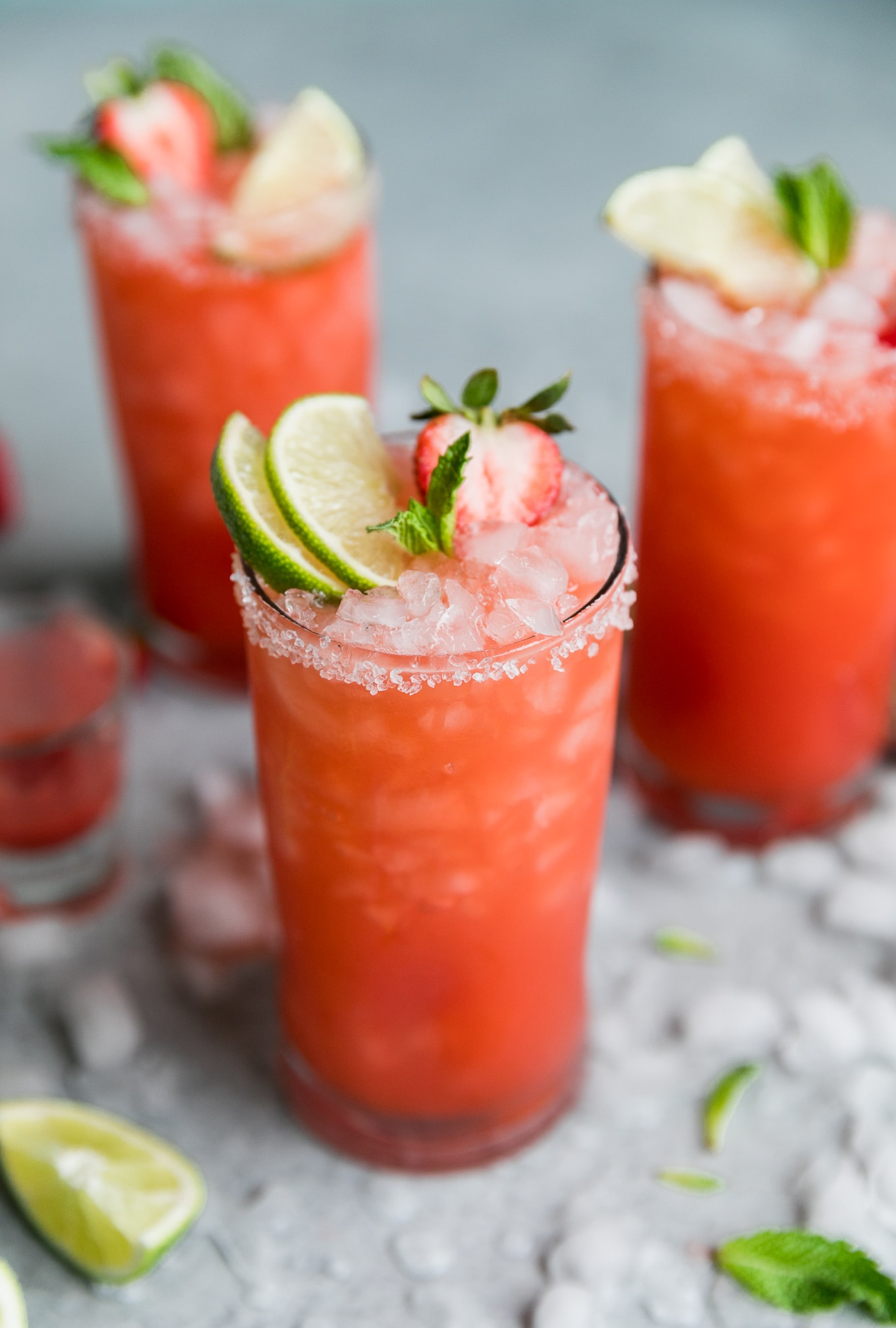 Close up shot of a strawberry margarita garnished with two lime slices, a mint sprig, and a halved strawberry with two margaritas and a shot glass in the background