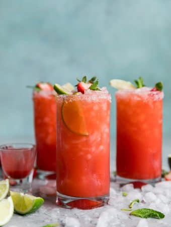 Forward facing shot of three strawberry margaritas with crushed ice on the table and a blue background