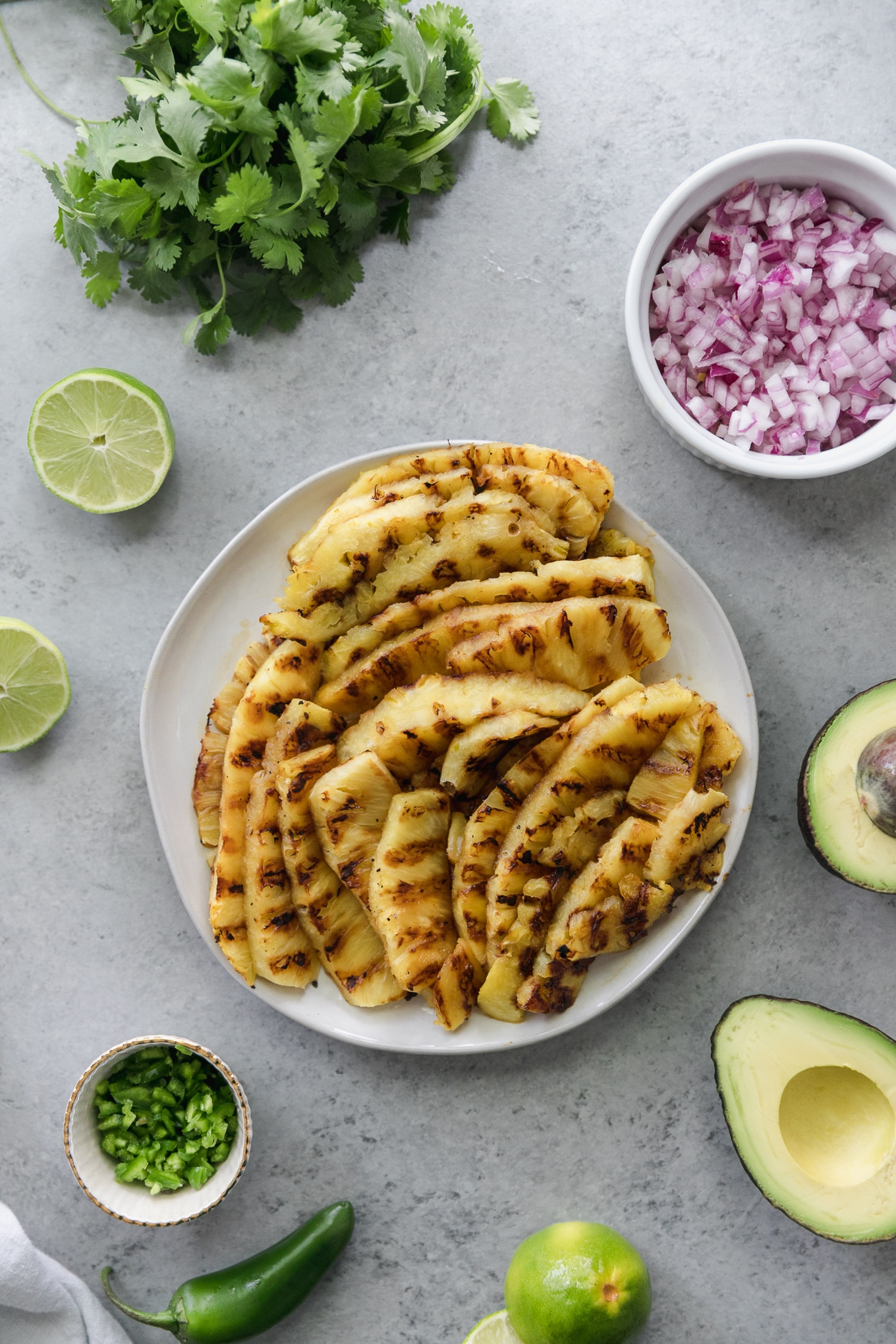 Over head shot of a plate of grilled pineapple spears, surrounded by a halved avocado, a bowl of chopped jalapeño, a bunch of cilantro, and a bowl of diced red onion