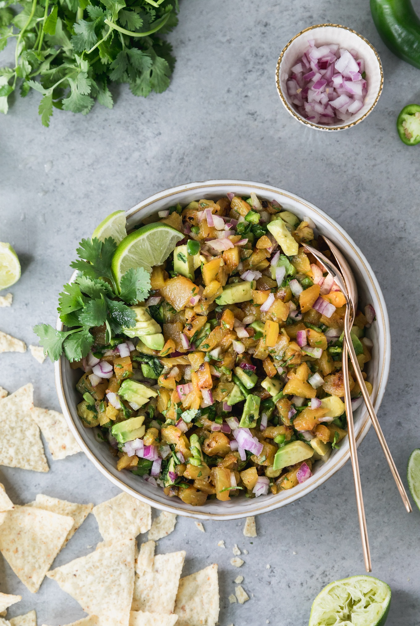 Overhead shot of a bowl of grilled pineapple avocado salsa with chips scattered to the left of the bowl, a bunch of cilantro in the top left, a bowl of diced red onion in the top right, and a squeezed lime half in the bottom right