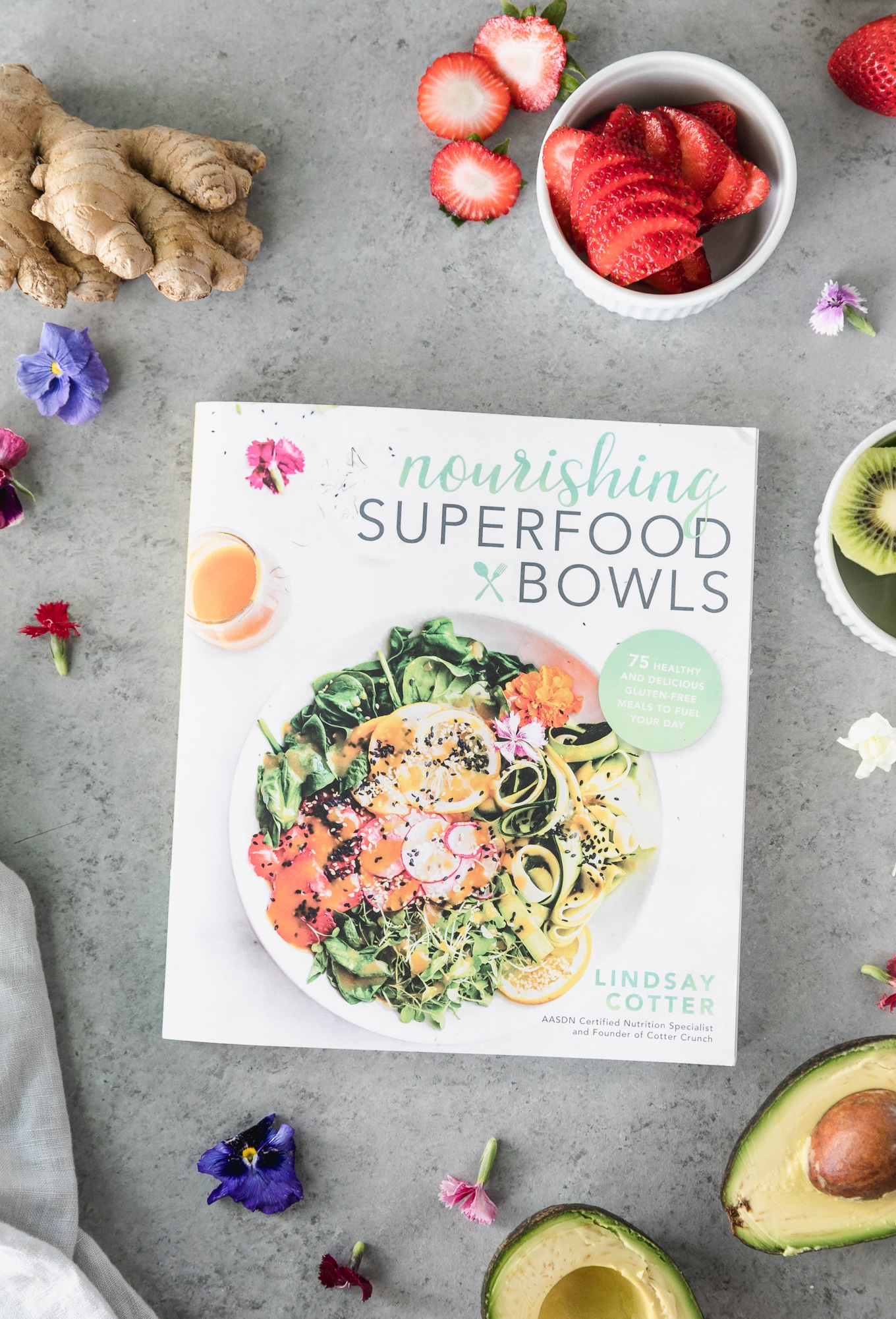 Overhead shot of the nourishing superfood bowls cookbook with bowls of sliced strawberries, kiwi, avocado, fresh ginger, edible flowers, and a linen around it