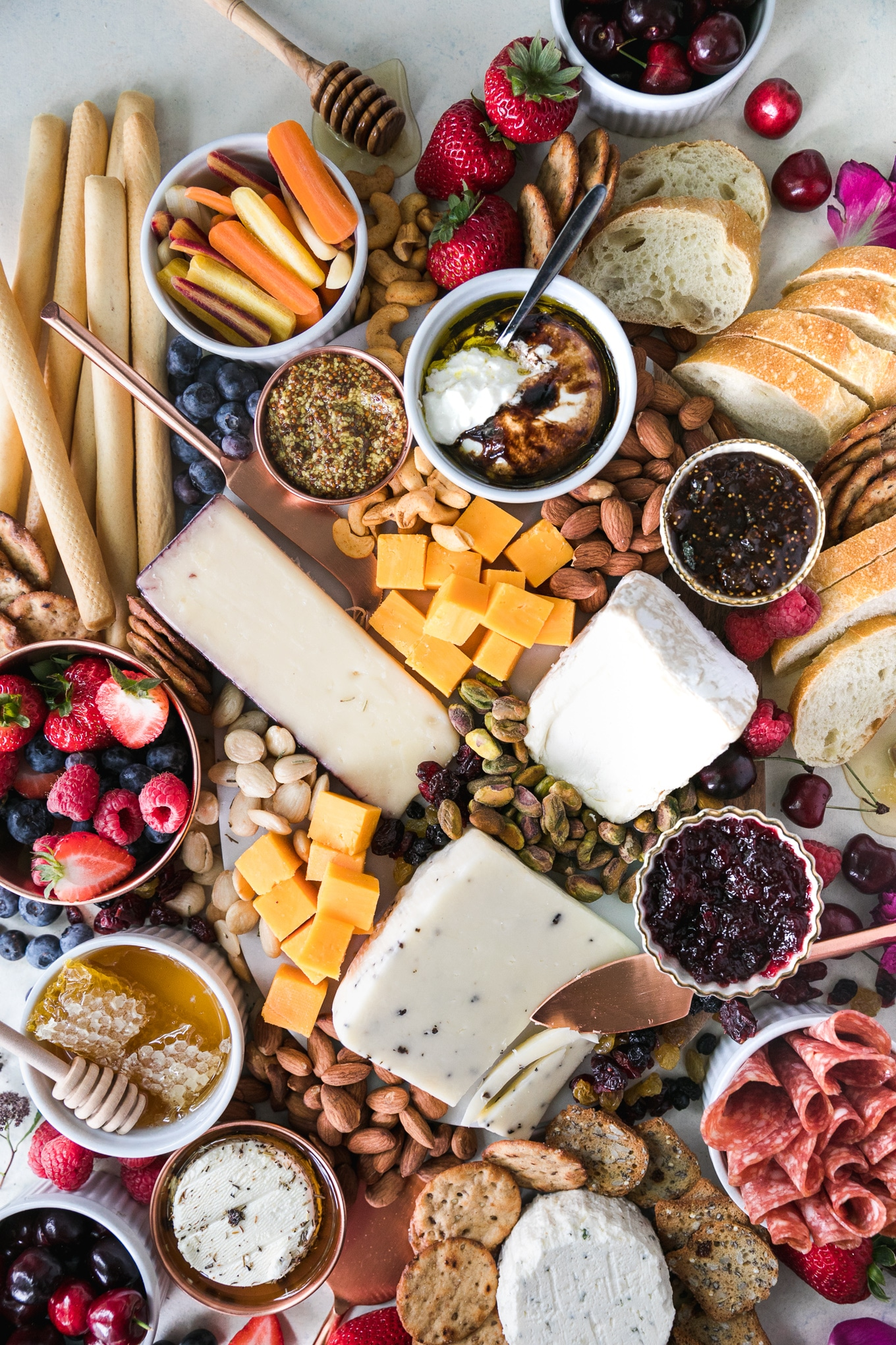 Overhead shot of a cheeseboard with various cheese, nuts, honey, preserves, honey, salami, crackers, bread, and fresh berries