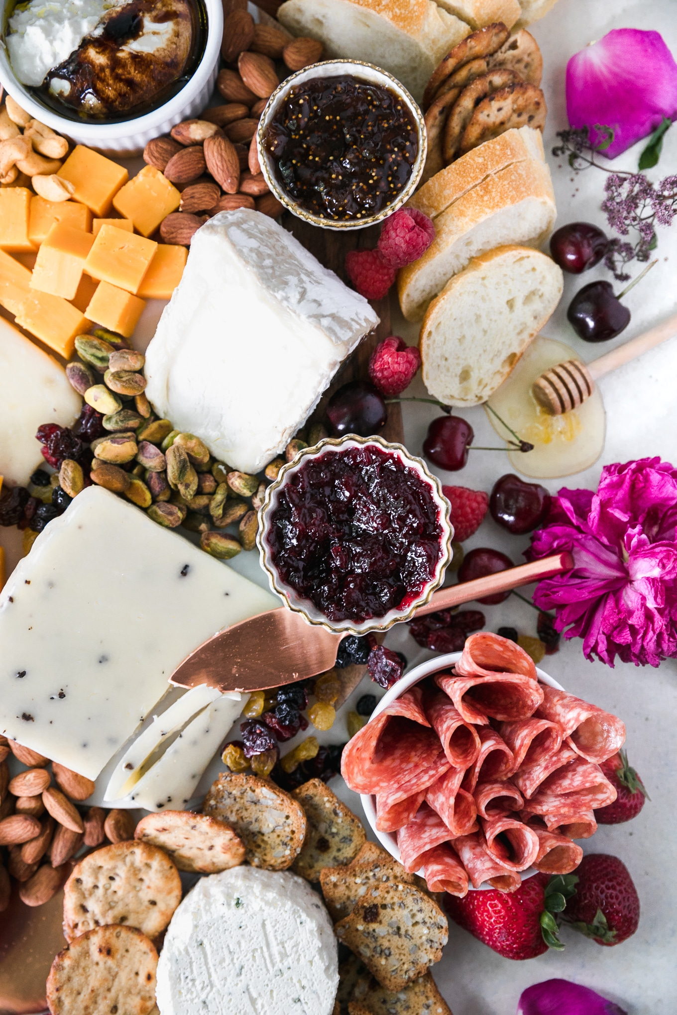 Overhead shot of a cheeseboard with various cheese, nuts, honey, preserves, honey, salami, crackers, bread, and fresh berries and a pink peony flower off to the side