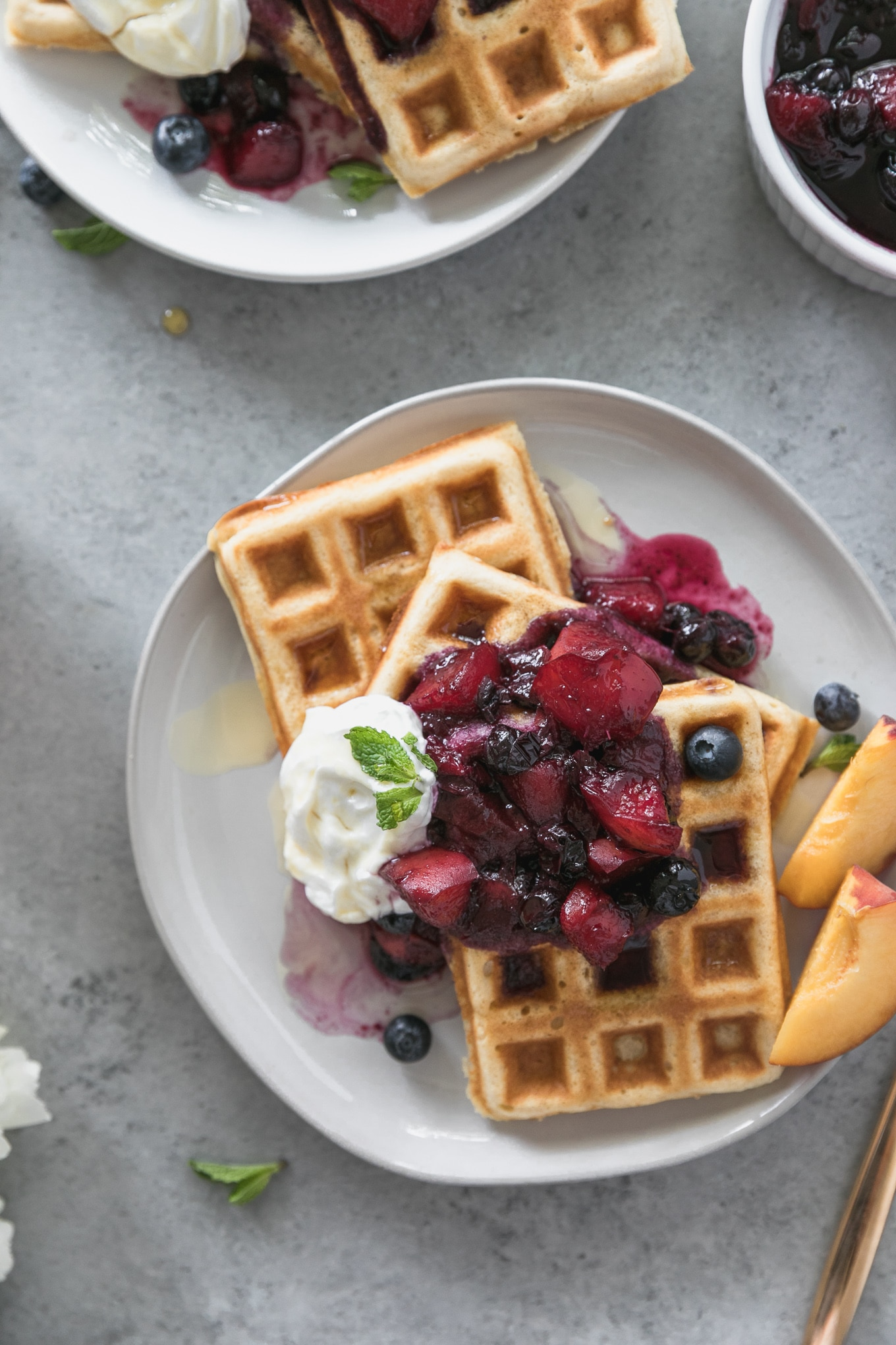 Overhead close up shot of a plate of buttermilk waffles topped with peach blueberry compute, sliced peaches on the side, and a dollop of greek yogurt and mint on top