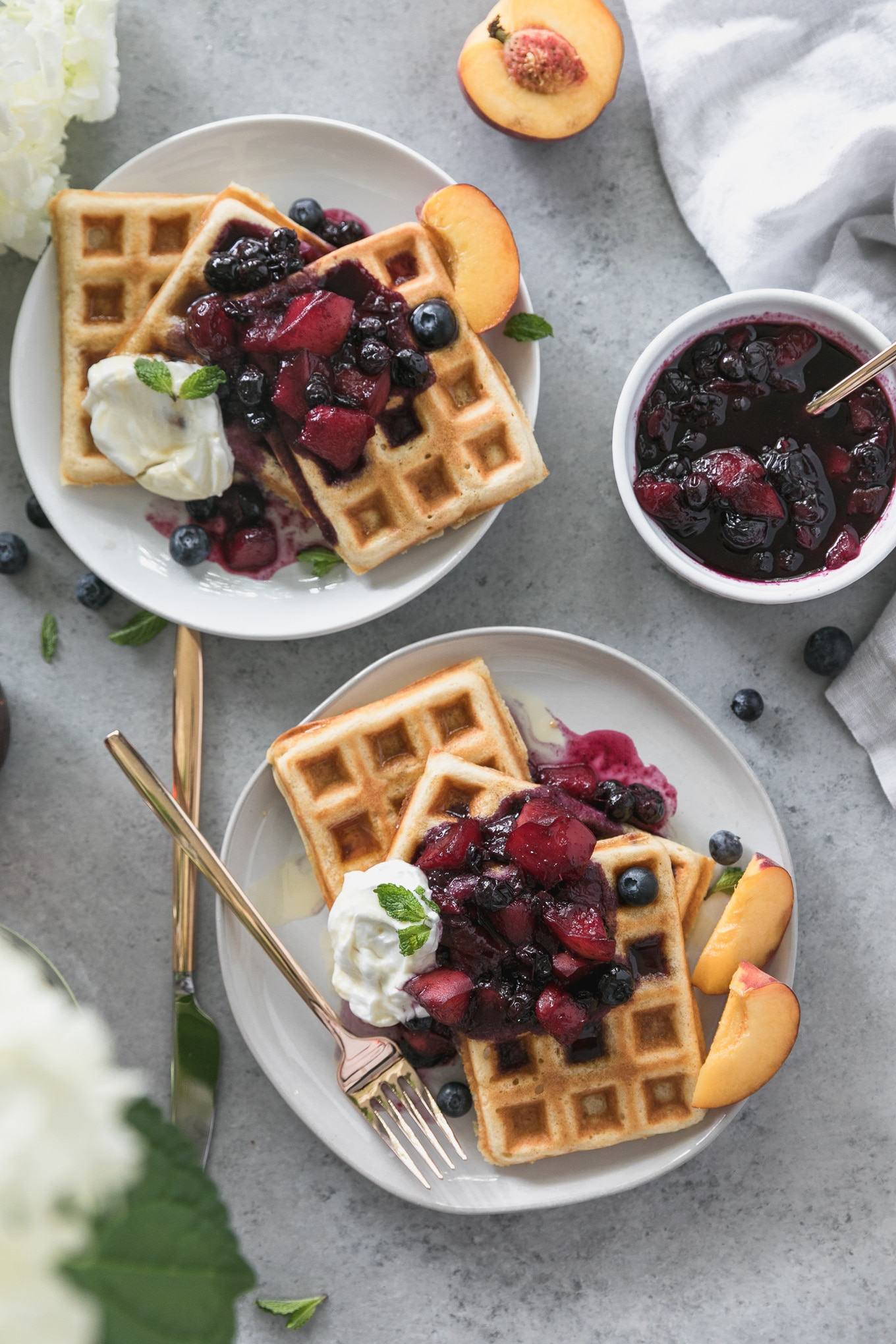 Overhead shot of two plates of waffles with peach blueberry compote on top, a bowl of compote in the top right, and white hydrangeas peeking out in the bottom left