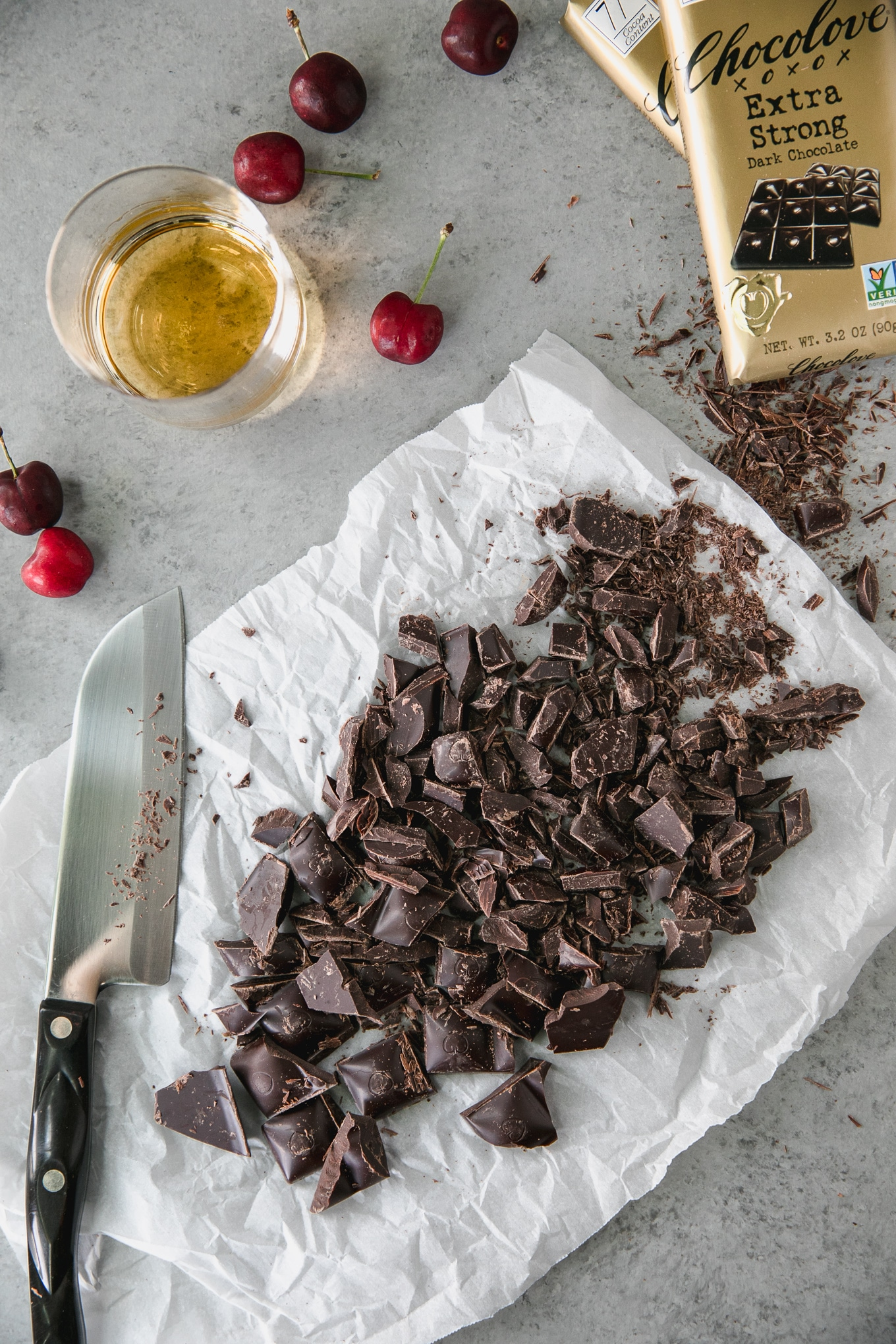 Overhead shot of a pile of chopped dark chocolate with a knife next to it as well as fresh cherries, a glass of bourbon, and a dark chocolate ba