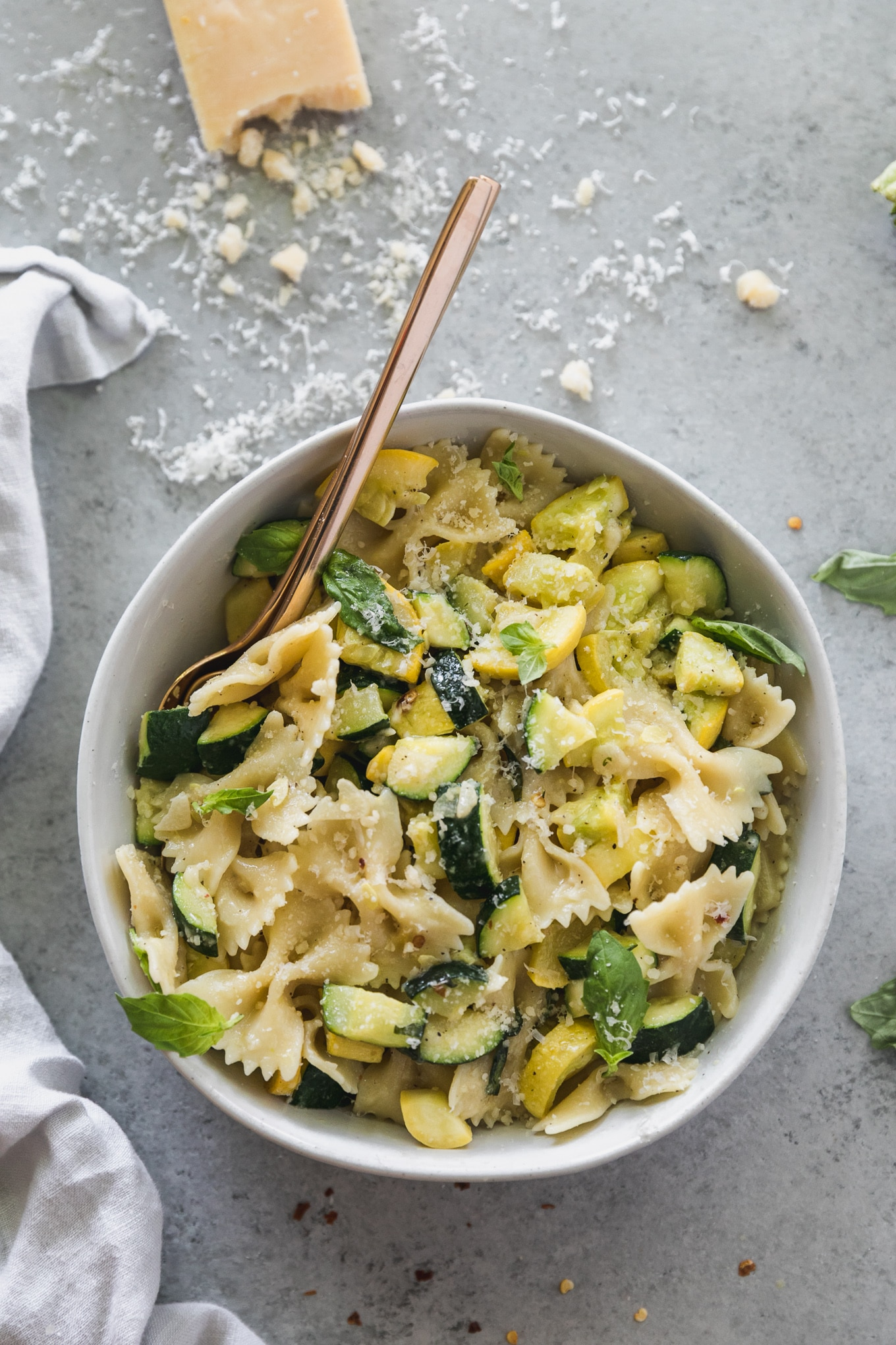 Overhead shot of a bowl of pasta with zucchini, summer squash, basil, parmesan, and a gold fork sticking out of the bowl