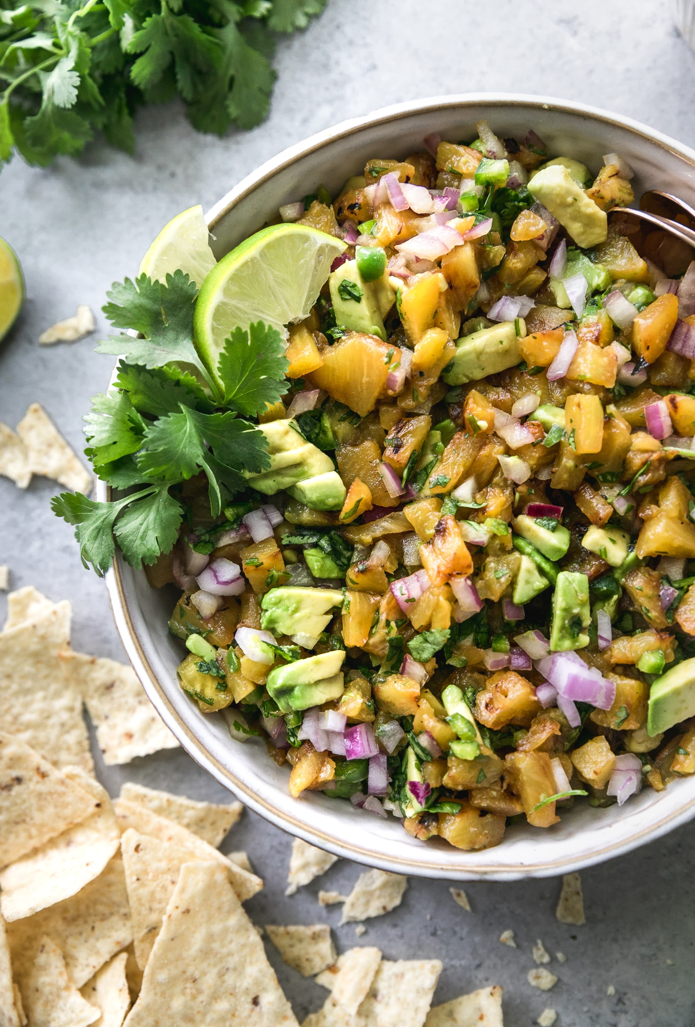 Overhead close up shot of a bowl of grilled pineapple avocado salsa with chips scattered around next to it