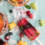 Overhead shot of a raspberry and blueberry popsicle on an aqua background with ice and fruit scattered around, and two glasses of rosé next to it