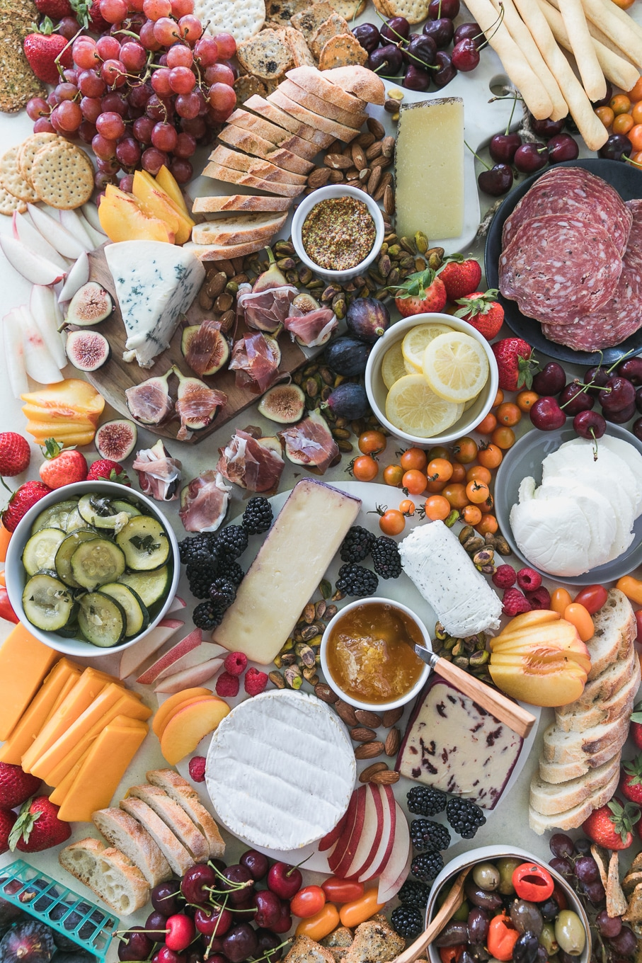 Overhead shot of a colorful cheeseboard filled with berries, prosciutto wrapped figs, marinated zucchini, nuts, berries, crackers, baguette, peaches, nectarines, grapes, honey, and preserved lemons