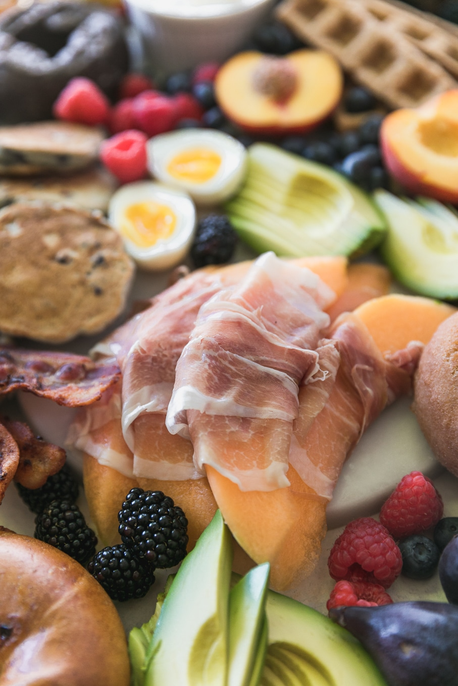 Close up shot of prosciutto wrapped melon, sliced avocado, soft boiled eggs, berries, mini pancakes, and fruit