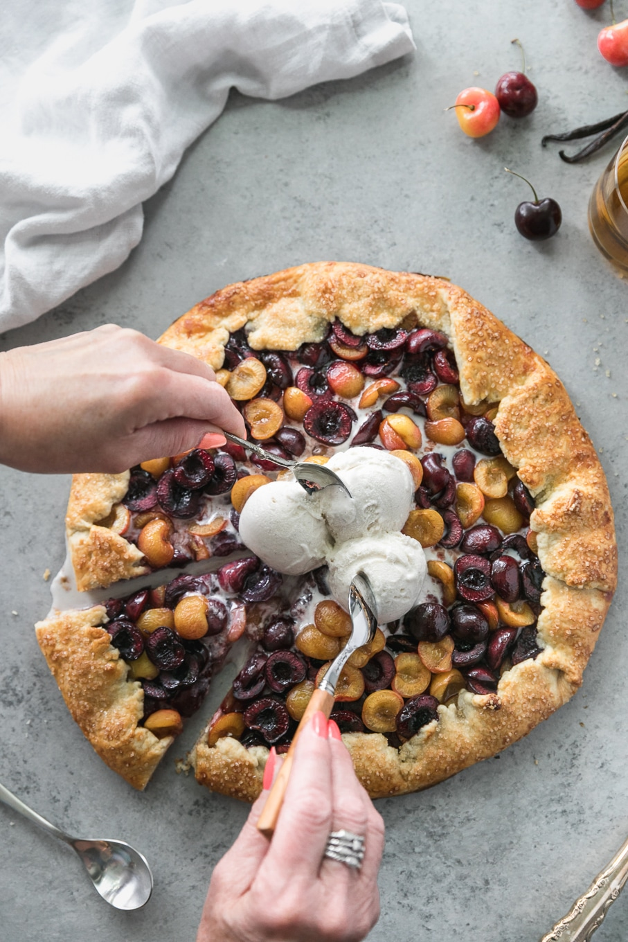 Overhead shot of a cherry galette with 3 scoops of ice cream on top with two hands reaching in with spoons to eat the ice cream
