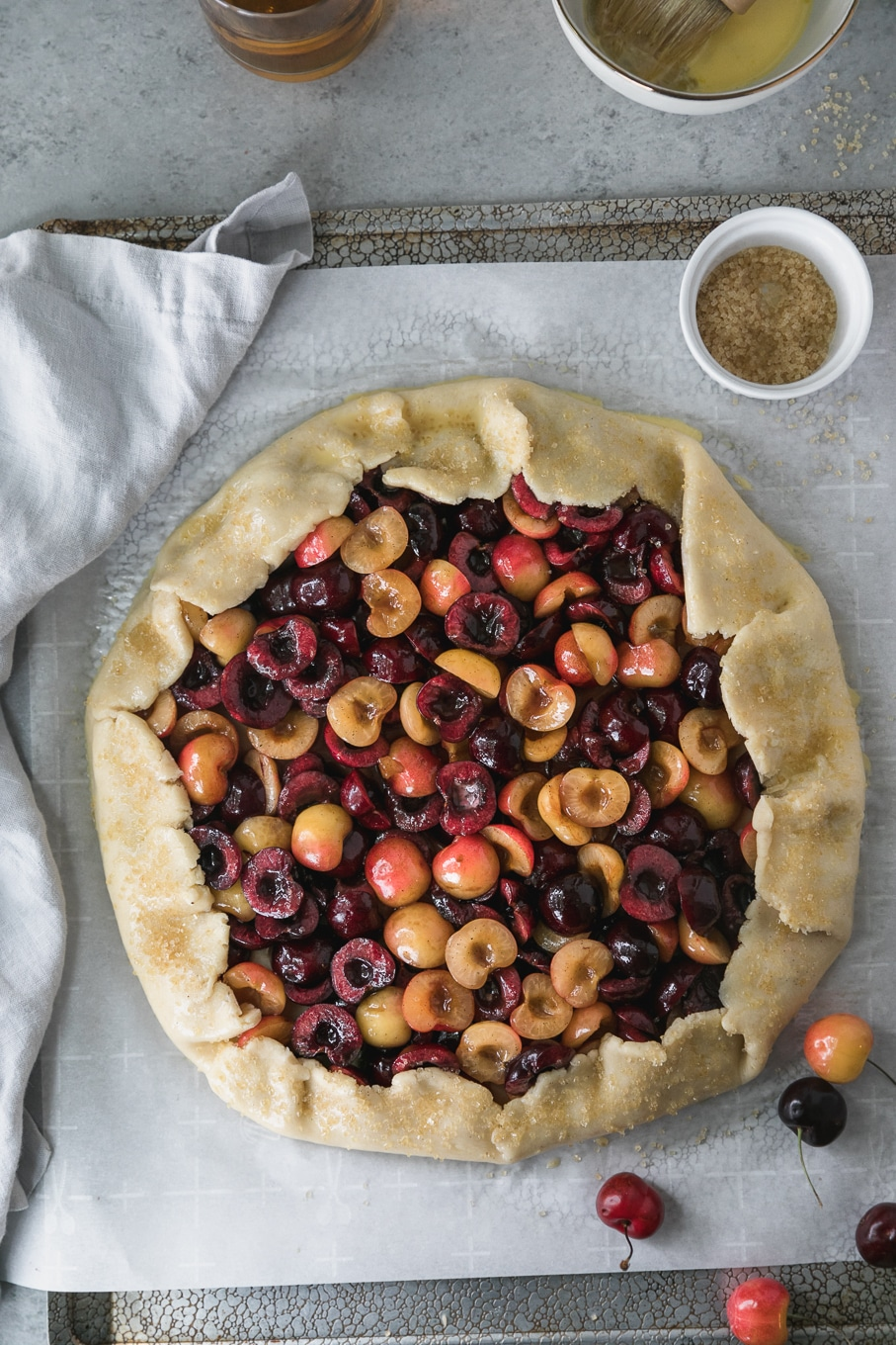 Overhead shot of a cherry galette on a baking sheet with a light grey napkin to the left