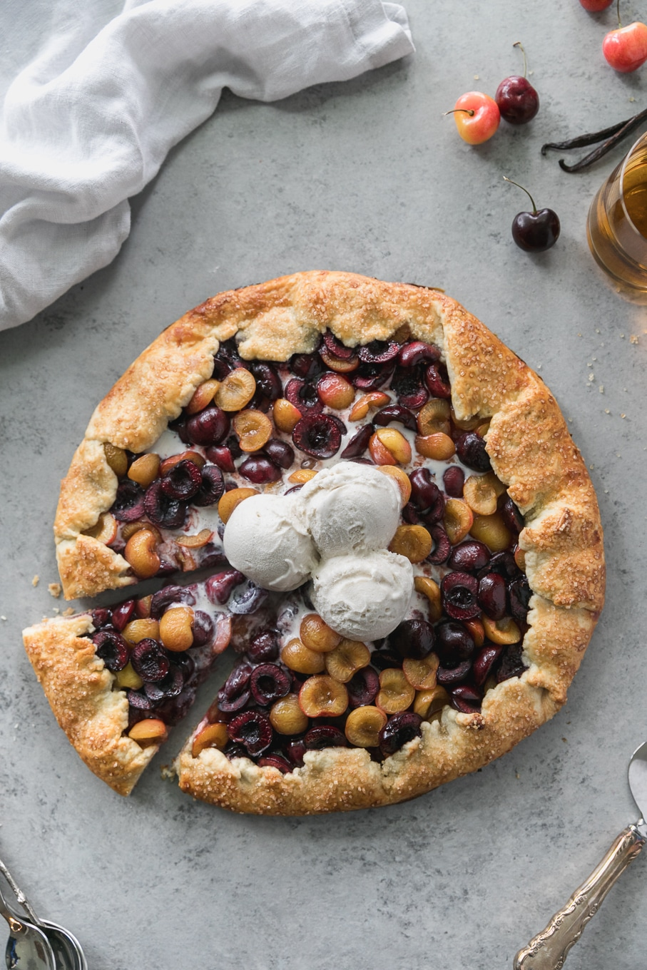 Overhead shot of a cherry galette with 3 scoops of ice cream on top with a slice being taken out