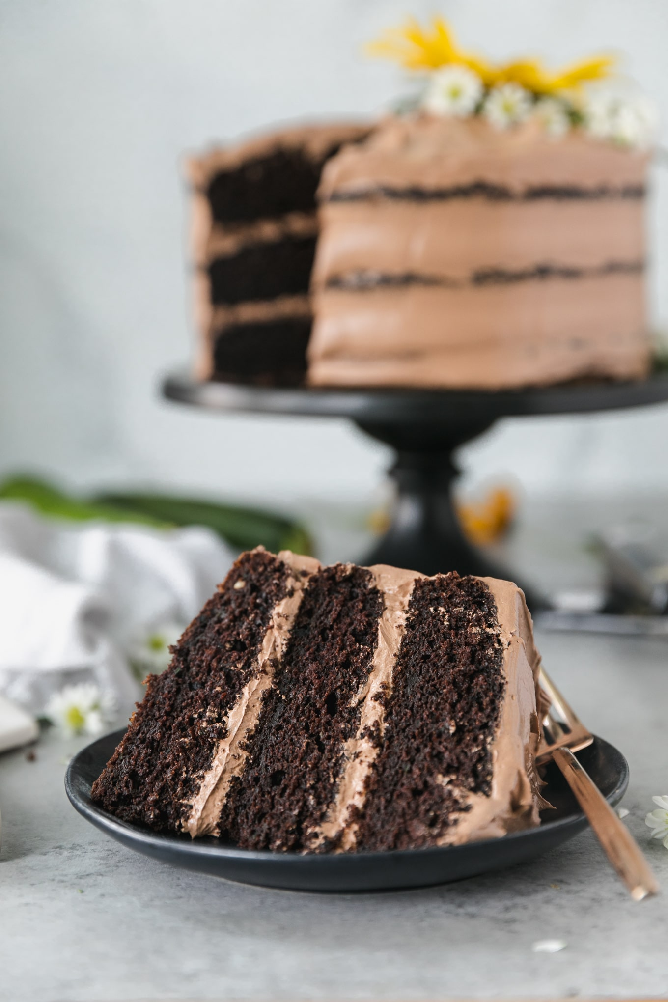 Close up shot of a piece of chocolate cake with the full later cake in the background on a black cake stand