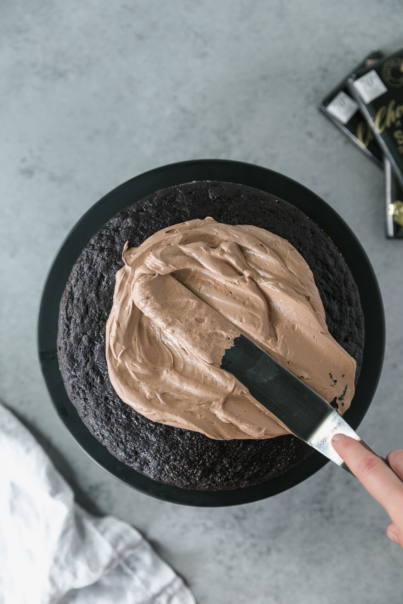 Overhead shot of chocolate buttercream being spread on a dark chocolate cake layer