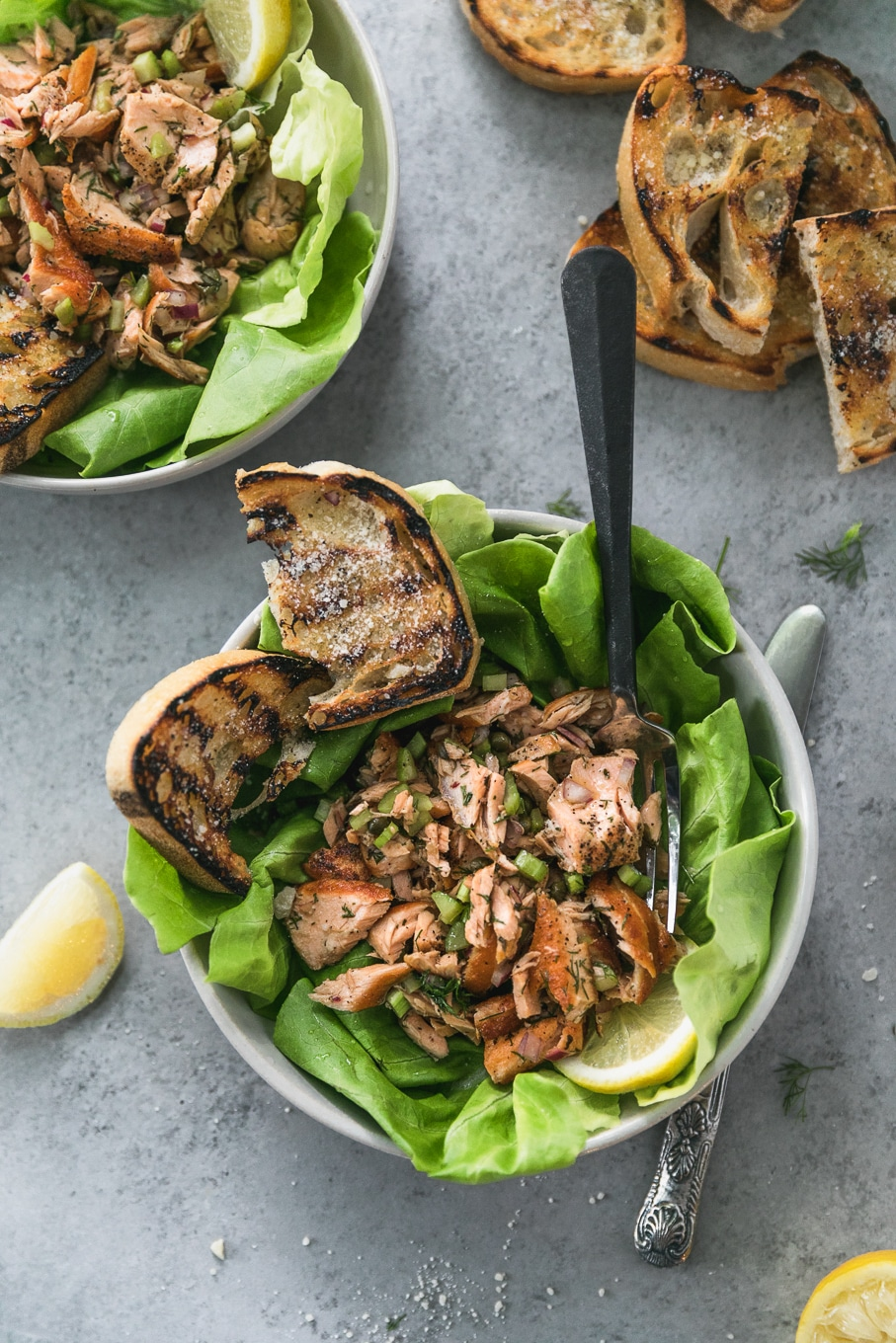 Overhead shot of two bowls filled with butter lettuce, flaked salmon and grilled garlic bread, with a lemon wedge and more slices of grilled garlic bread off to the side