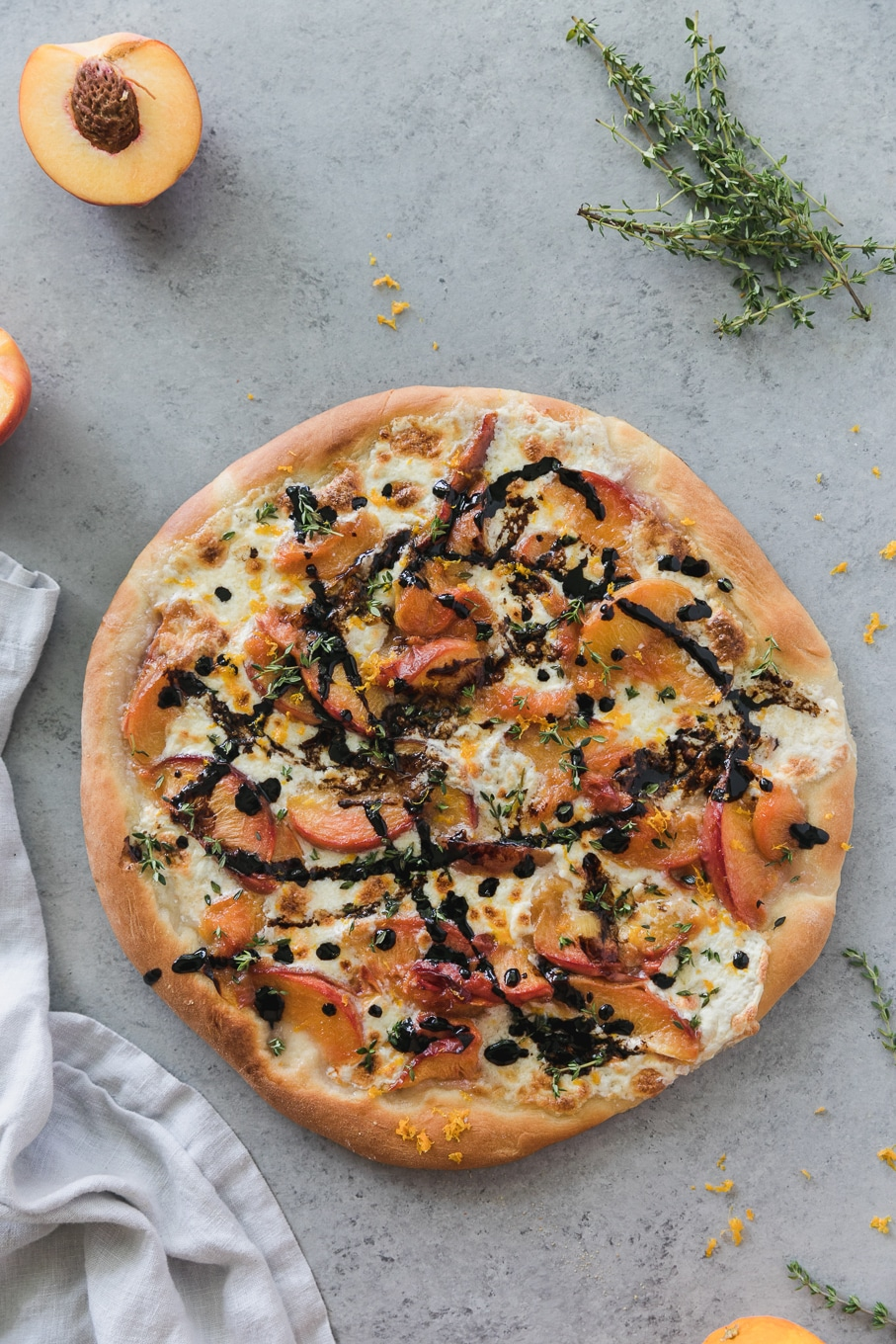 Overhead shot of a pizza topped with peaches, balsamic glaze, thyme, and burrata
