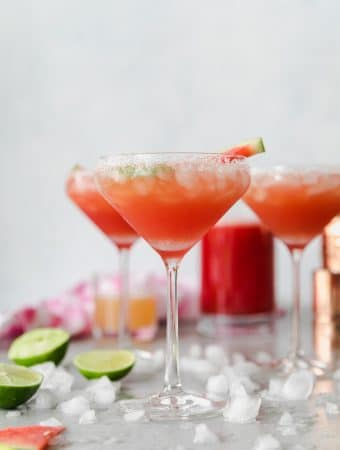 Forward facing shot of 3 tall margarita glasses filled with a deep reddish pink margarita and crushed ice and limes scattered around and a copper shaker and glass of watermelon juice in the background