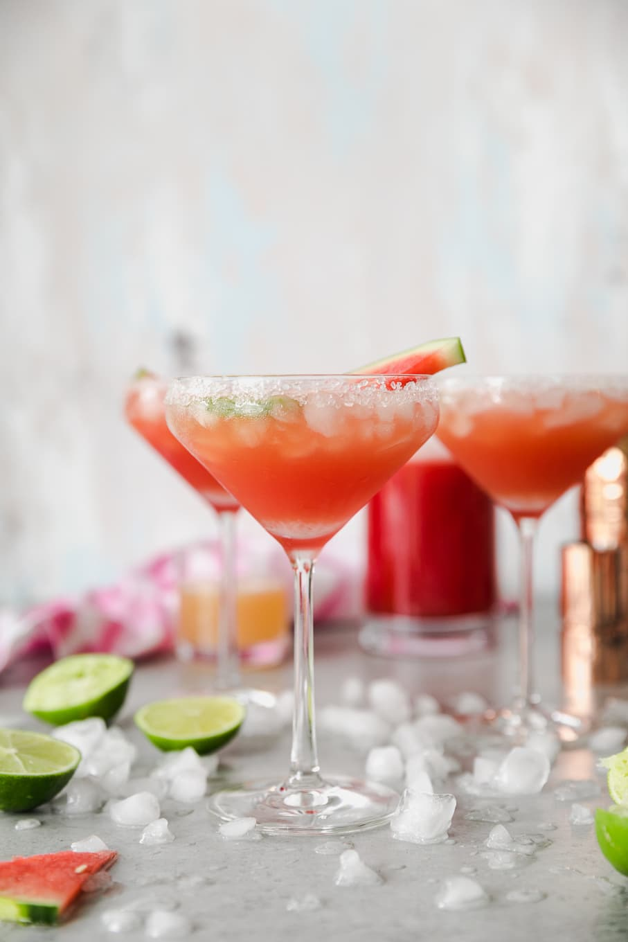 Forward facing shot of 3 tall margarita glasses filled with a deep reddish pink margarita and crushed ice and limes scattered around