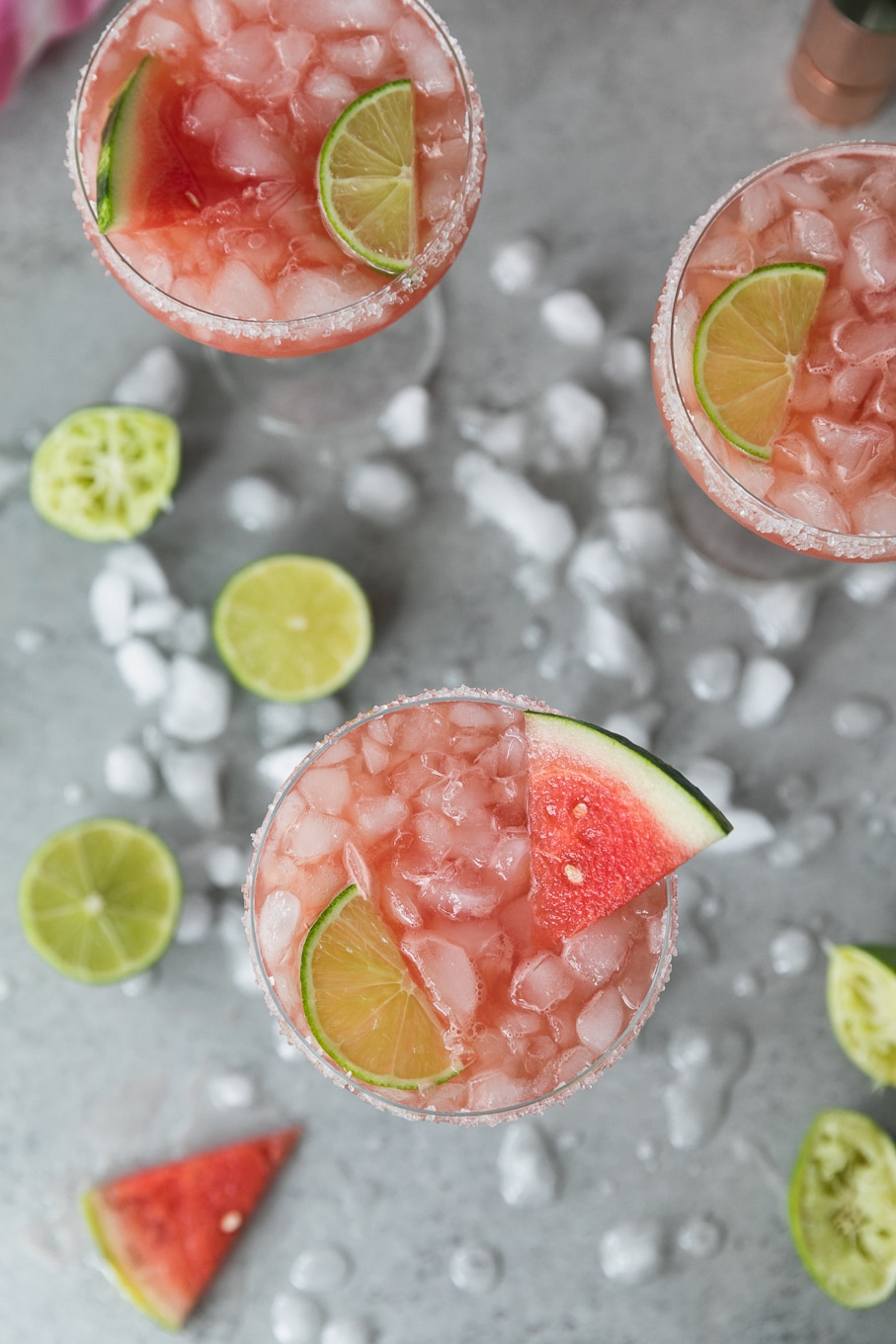 Overhead shot of 3 tall margarita glasses filled with crushed ice and pink watermelon grapefruit margaritas garnished with sliced watermelon and lime