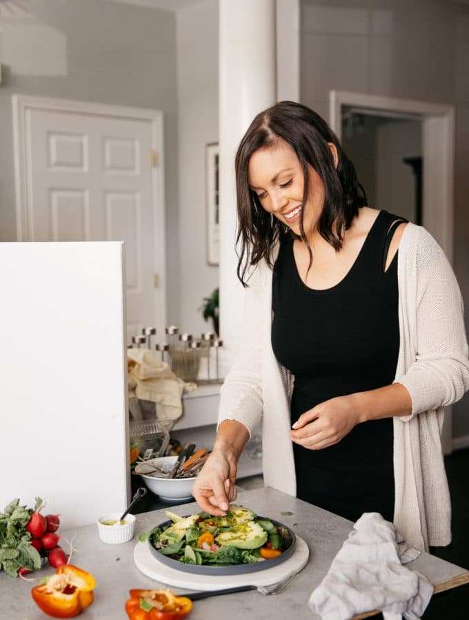 Photo of woman smiling and styling a colorful salad