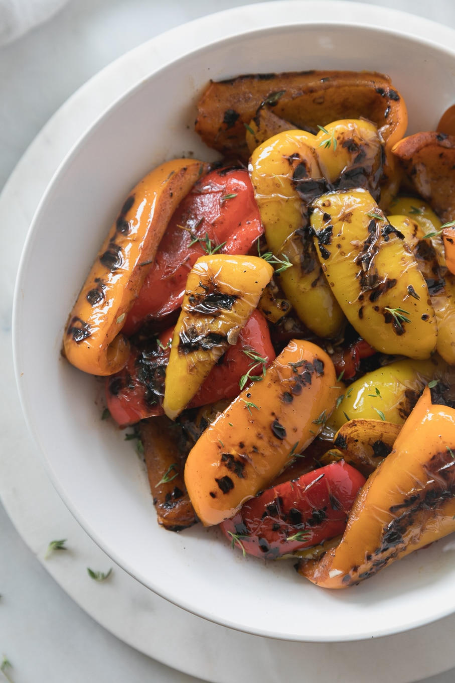Overhead close up shot of a bowl of grilled peppers sprinkled with fresh thyme