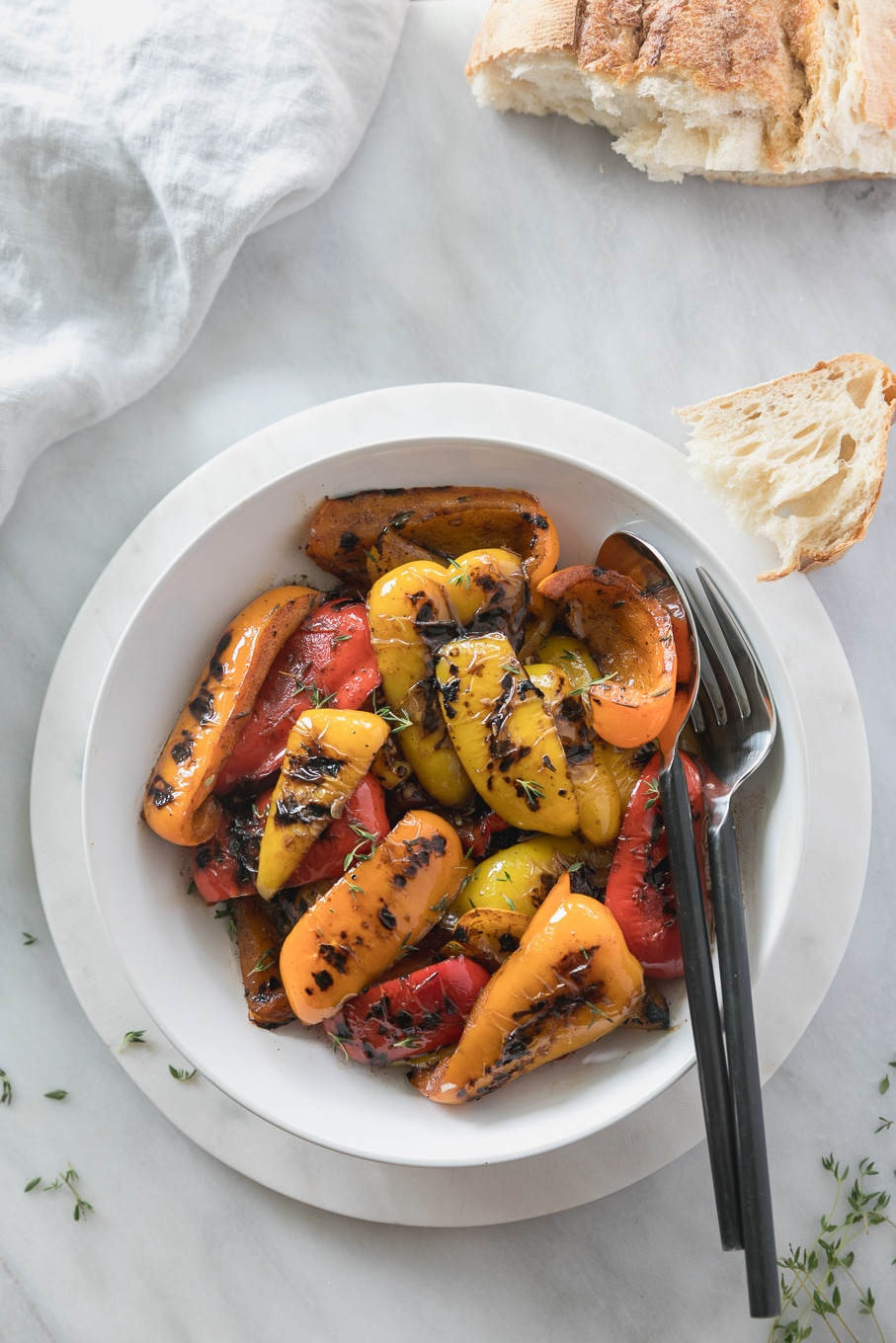 Overhead shot of a bowl of grilled peppers with a large spoon and fork in the bowl, as well as a half piece of bread off to the side