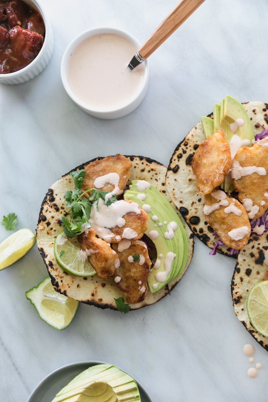 Overhead close up shot of 3 crispy fish tacos topped with avocado, cilantro, and chipotle lime crema