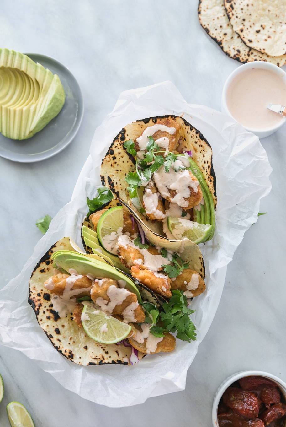 Overhead shot of 3 crispy fish tacos in a basket topped with avocado, cilantro, and chipotle lime crema
